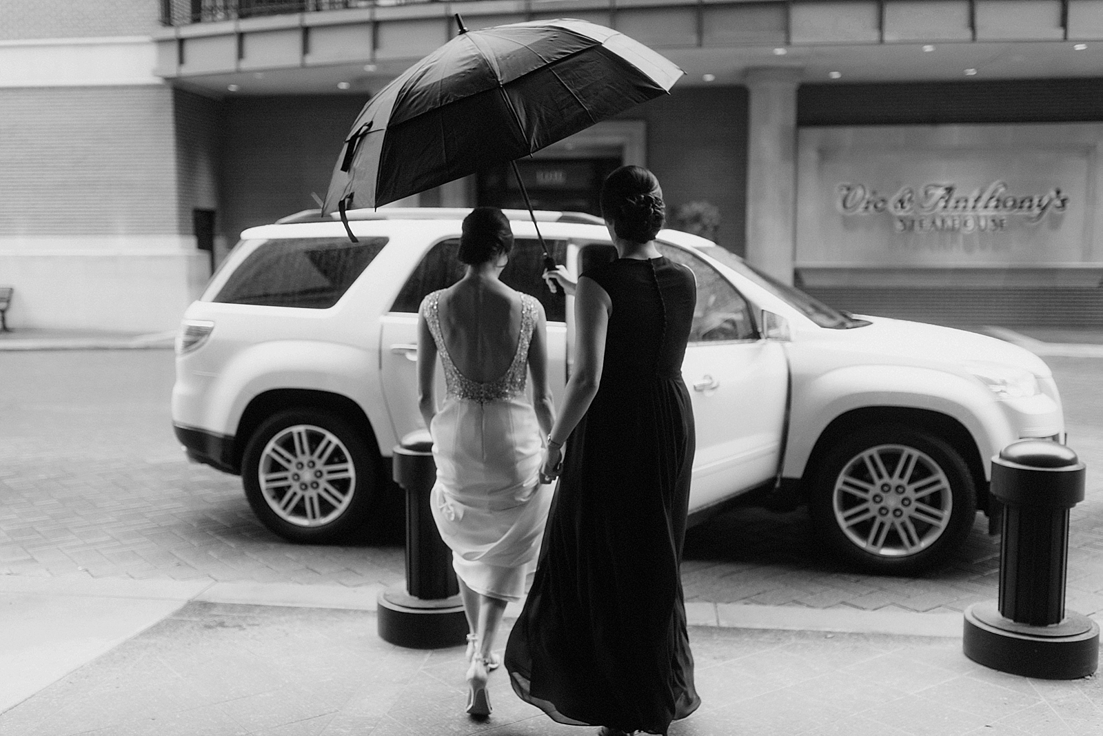 Timeless moment as bride enters a waiting car for her rainy Houston wedding