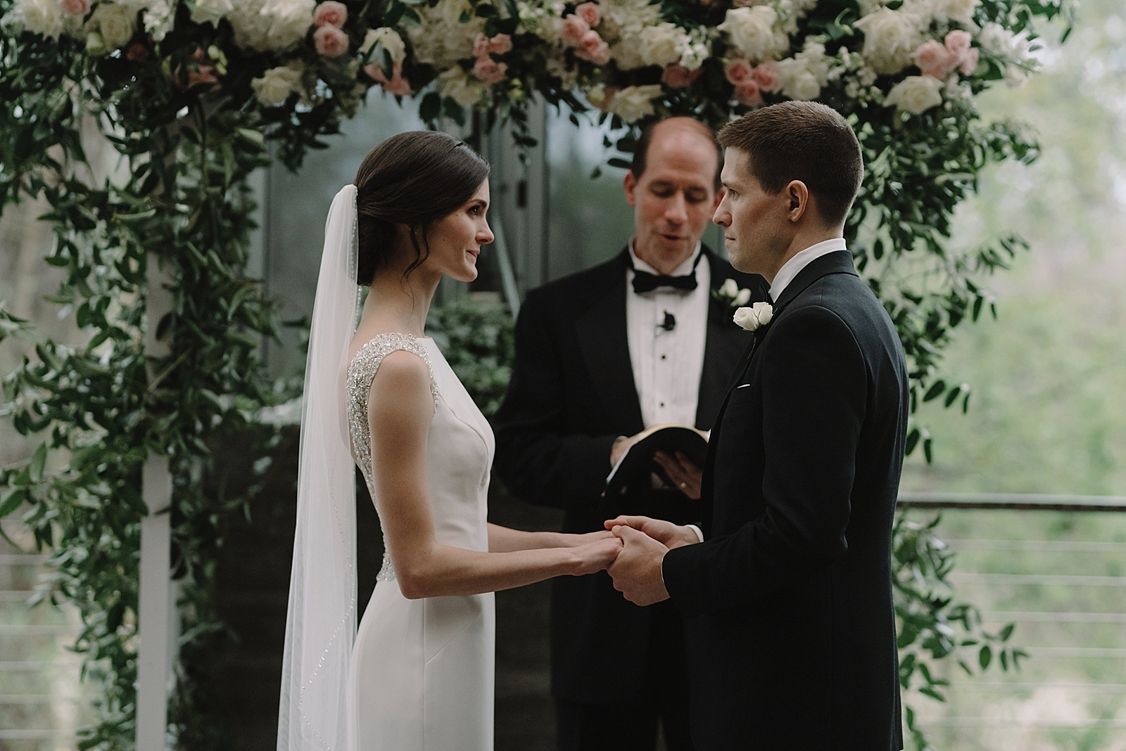 Emotive ceremony moment with a greenery altar with pink and white floral tones