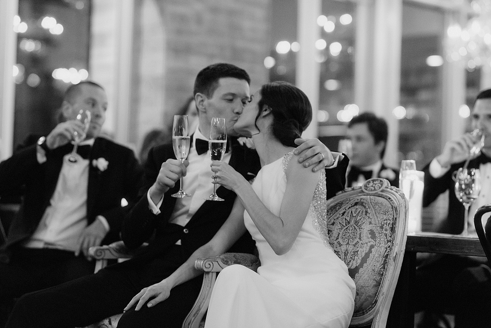 Romantic kiss during a wedding toast at a candlelit reception