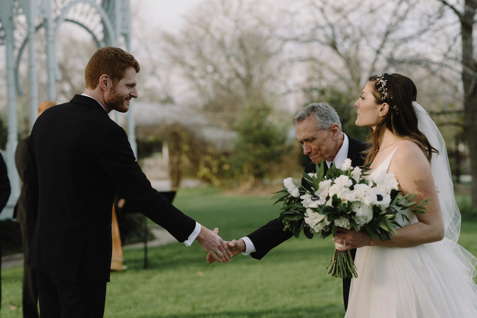 An emotional handshake between the father of the bride and groom at a wedding ceremony