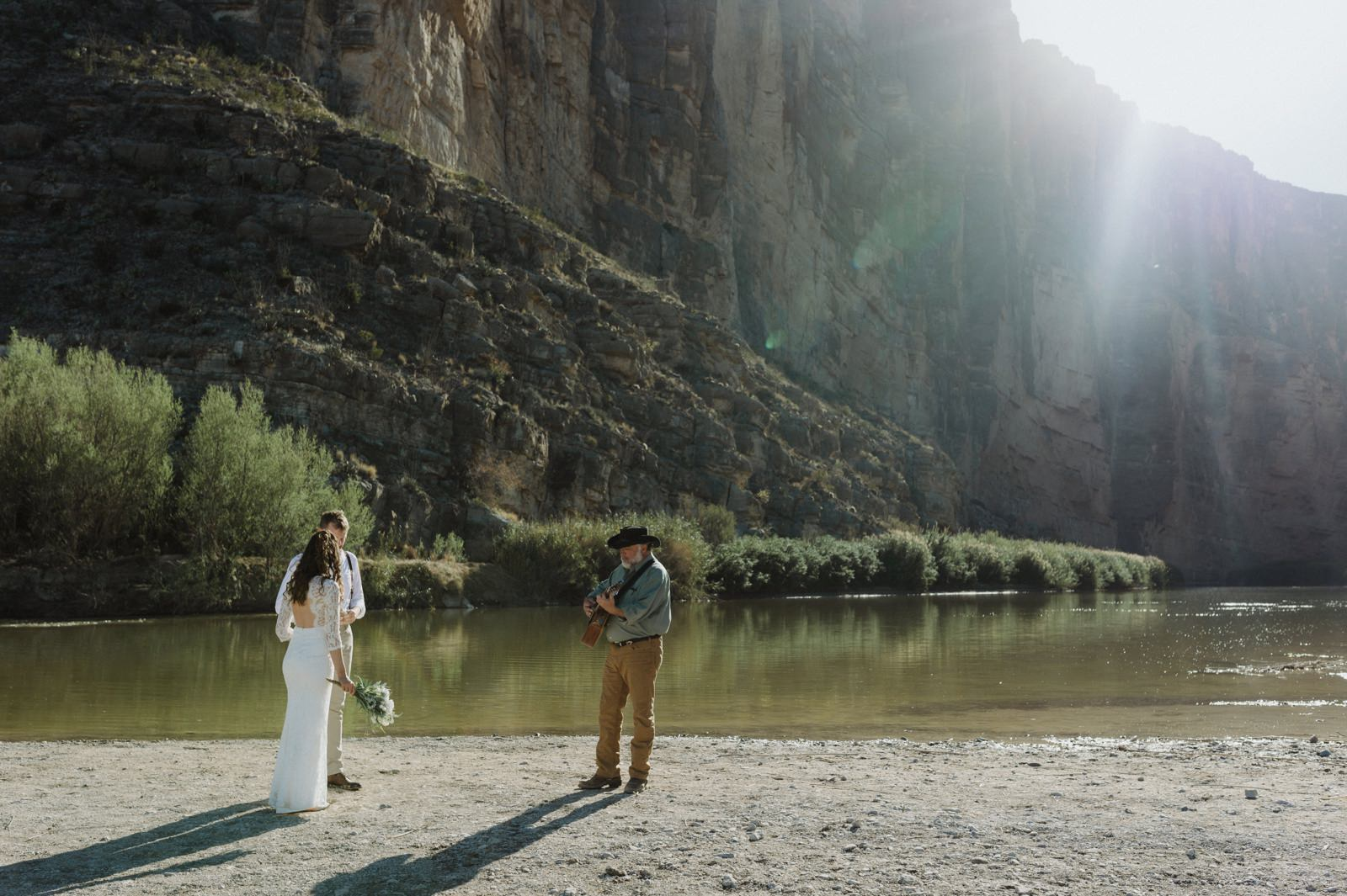 An eloping couple and the guitar playing commissioner prepping for their Big Bend elopement in a canyon