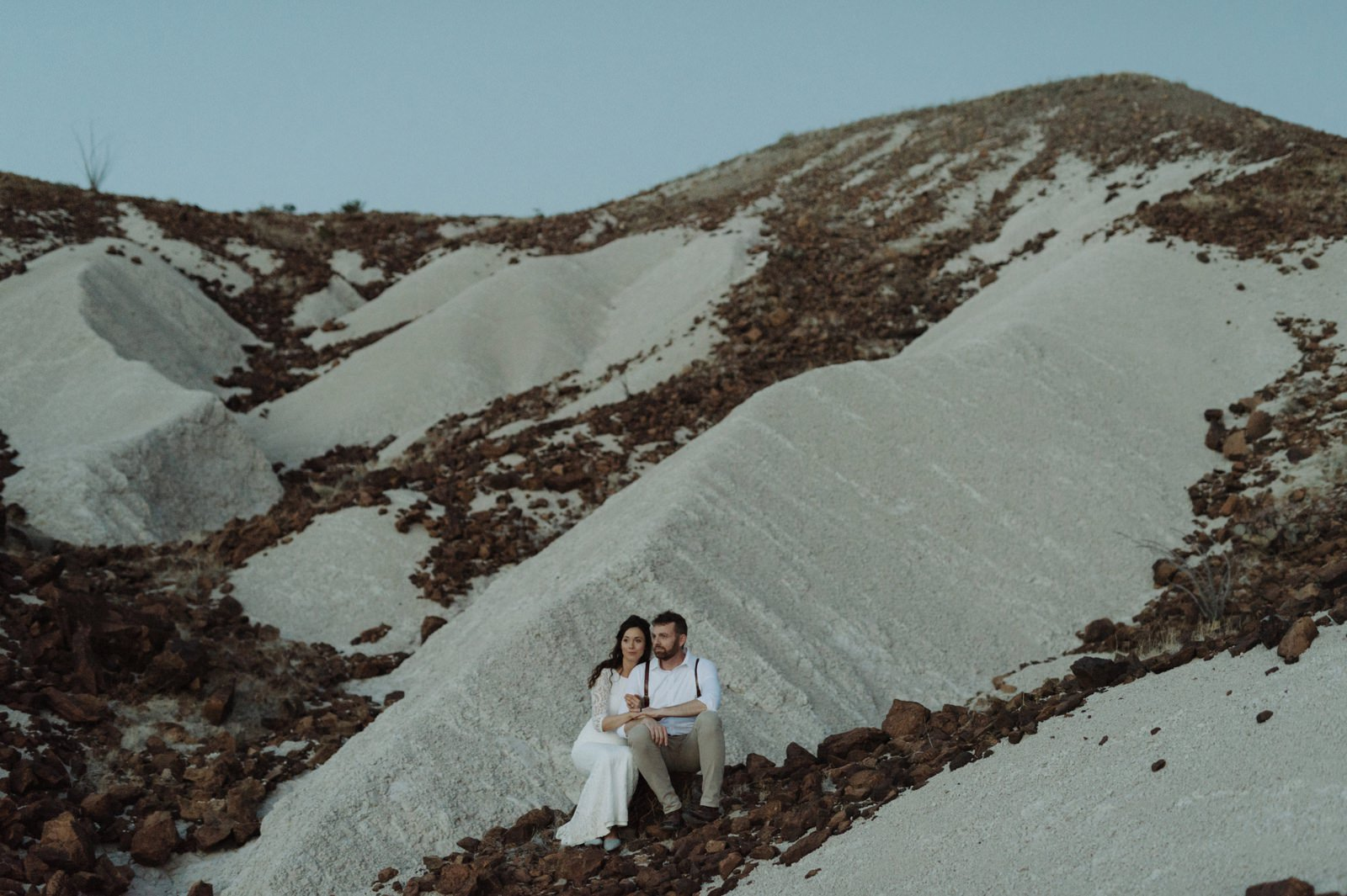 Adventurous elopement couple sitting on the white sand dunes in the heart of Big Bend