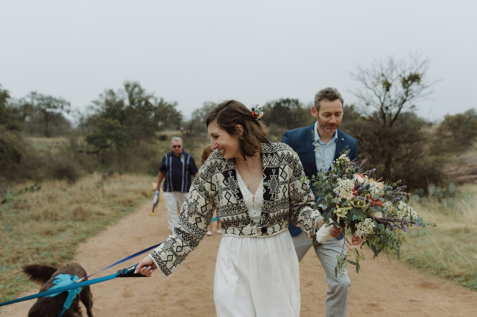 Eloping bride wearing a white and black patterned shawl walking her dog to their Enchanted Rock ceremony
