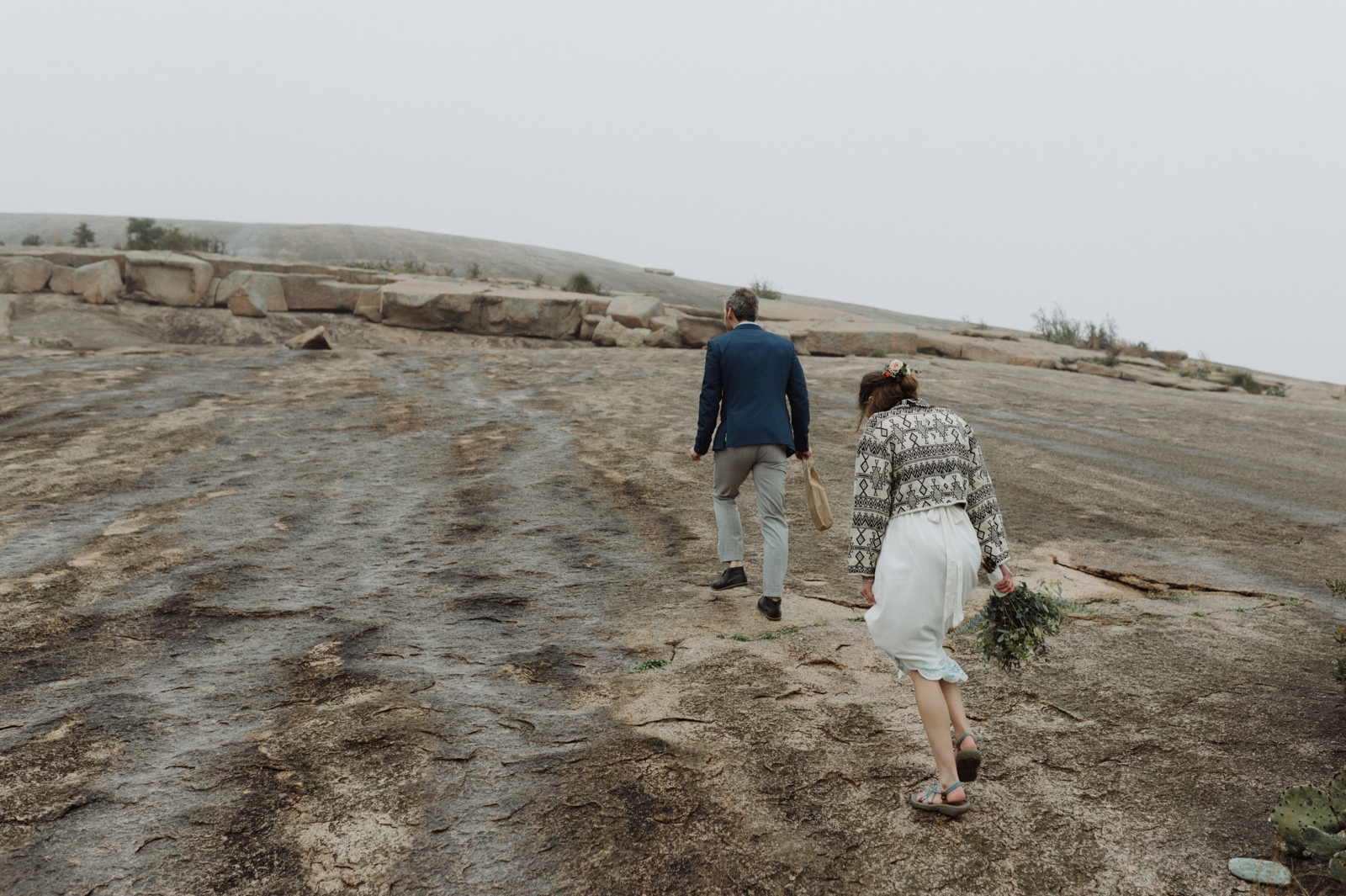 Adventurous wedding couple hiking the trail up Enchanted Rock