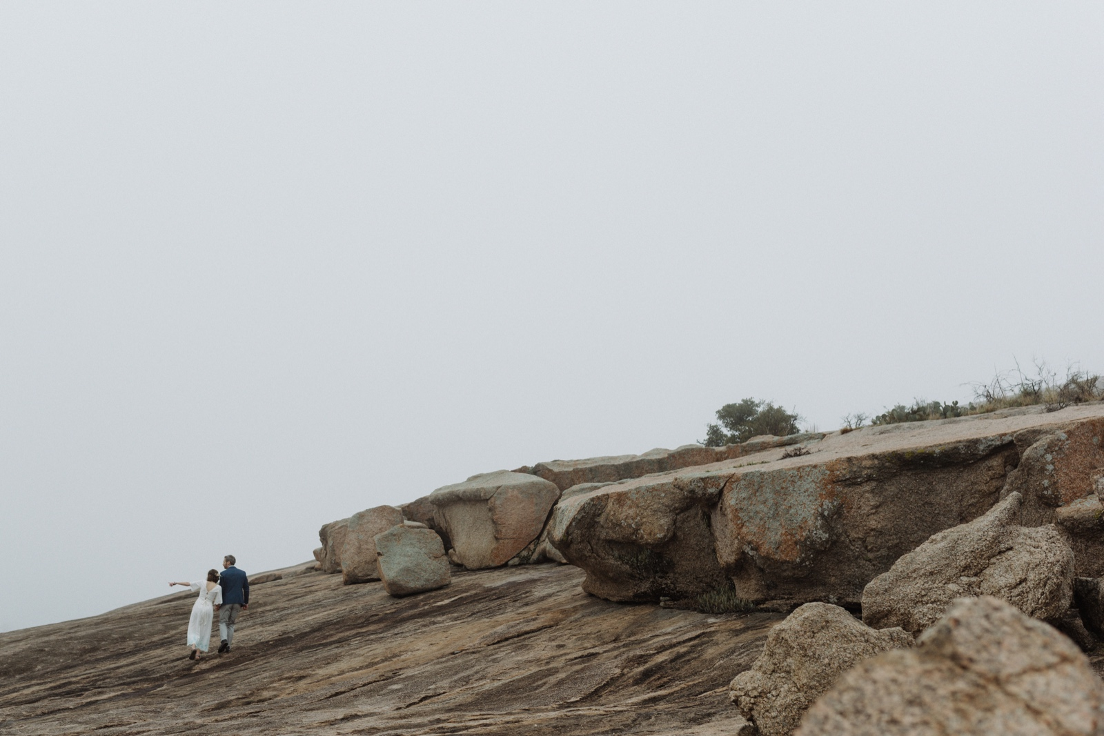 Hikers who eloped exploring the top of the Enchanted Rock dome in Texas