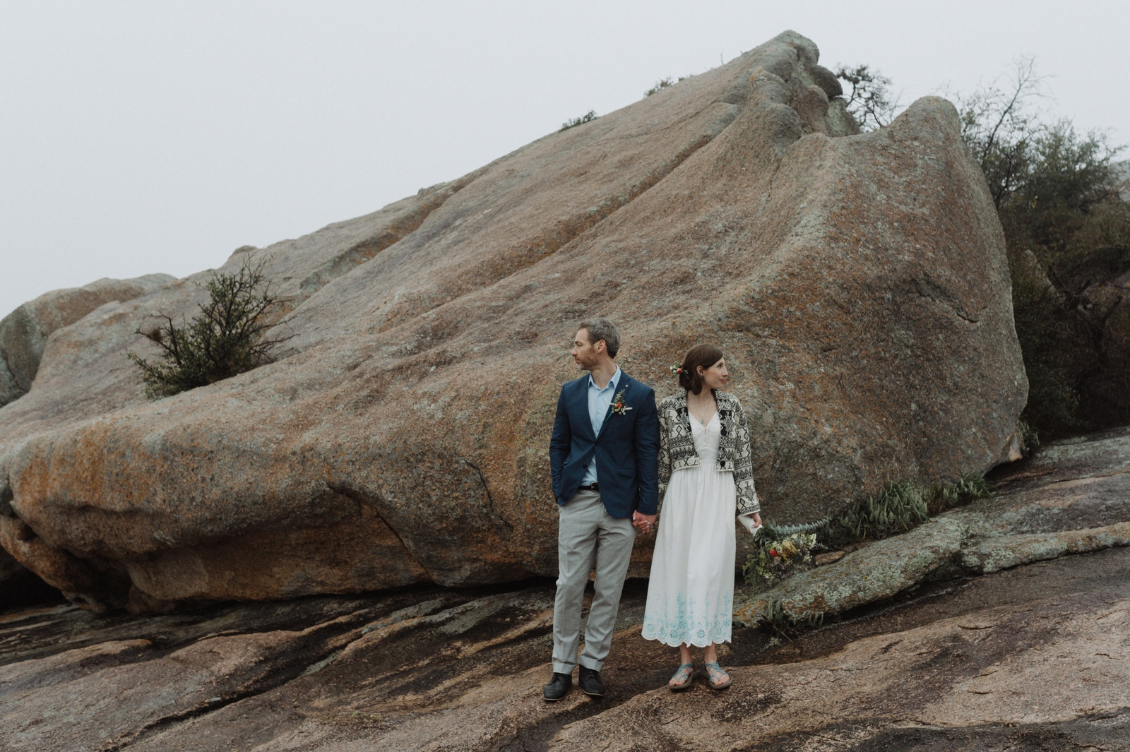 An elopement at Enchanted Rock with a simple white dress and blue detailed hiking sandals