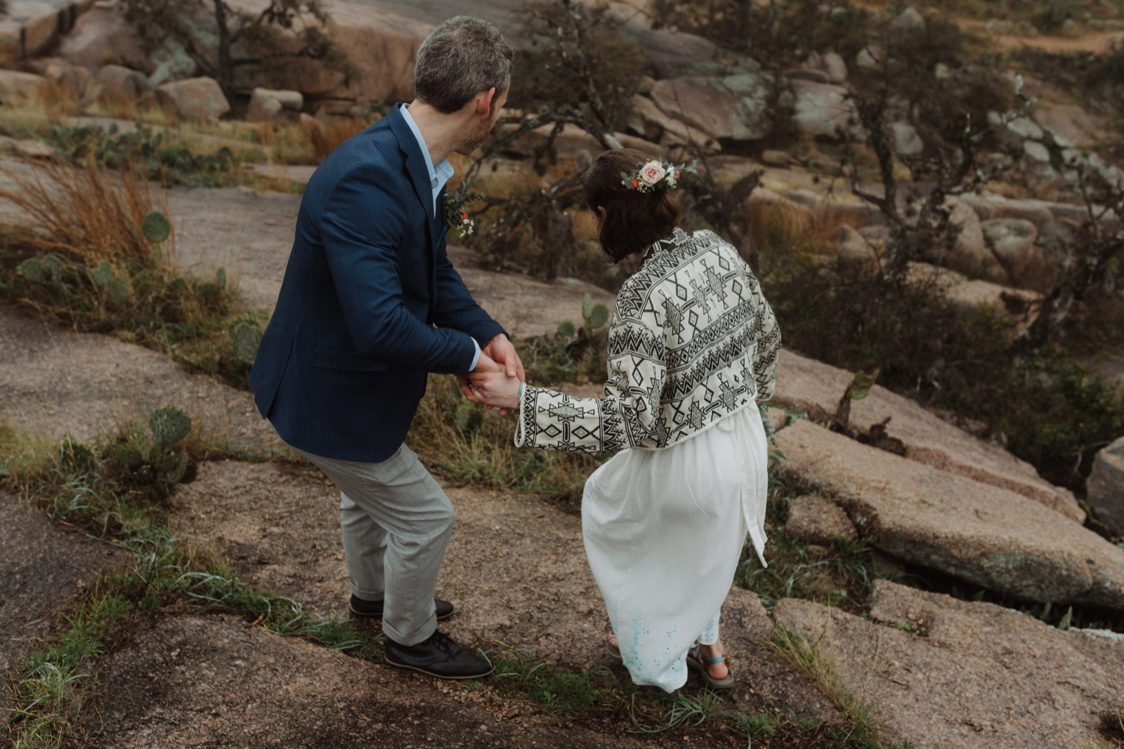 Stylish couple who eloped descending the pink granite of Enchanted Rock