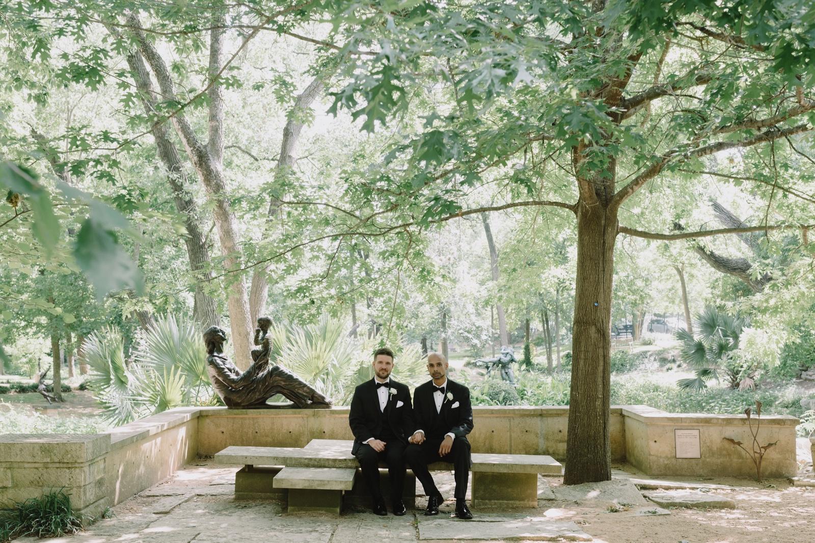 Creative wedding portraits in the Umlauf Sculpture Garden for two grooms