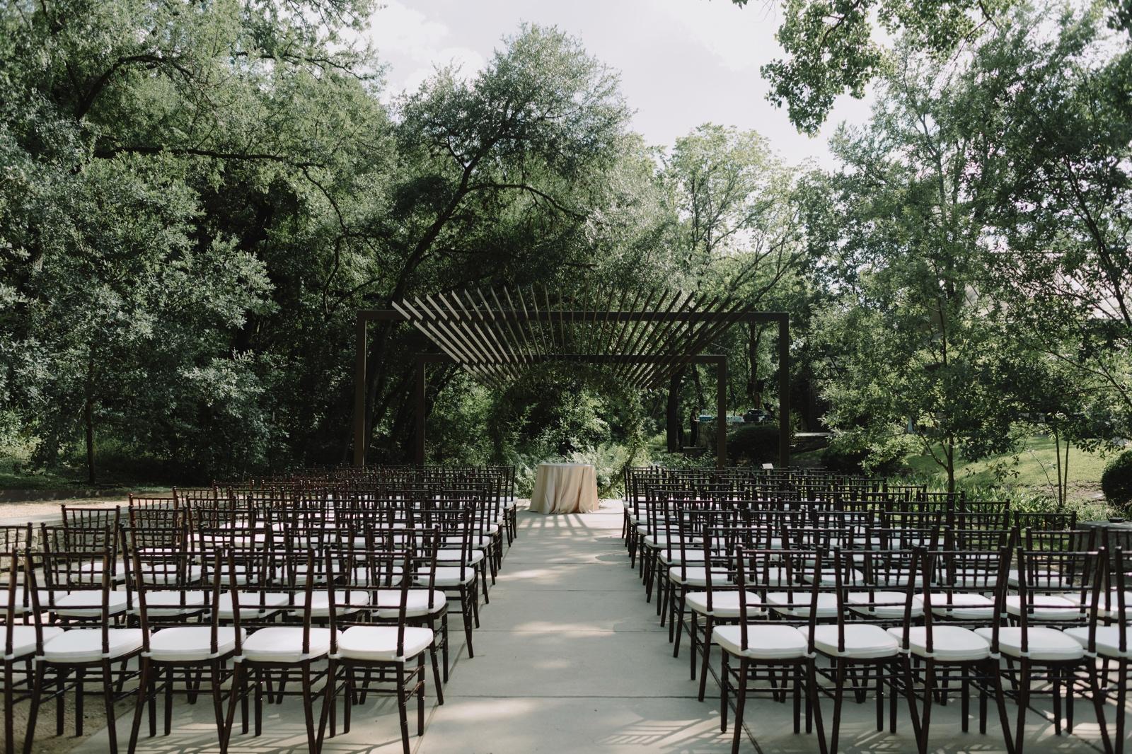 Umlauf Sculpture Garden wedding ceremony setup under the arbor with chevalier chairs