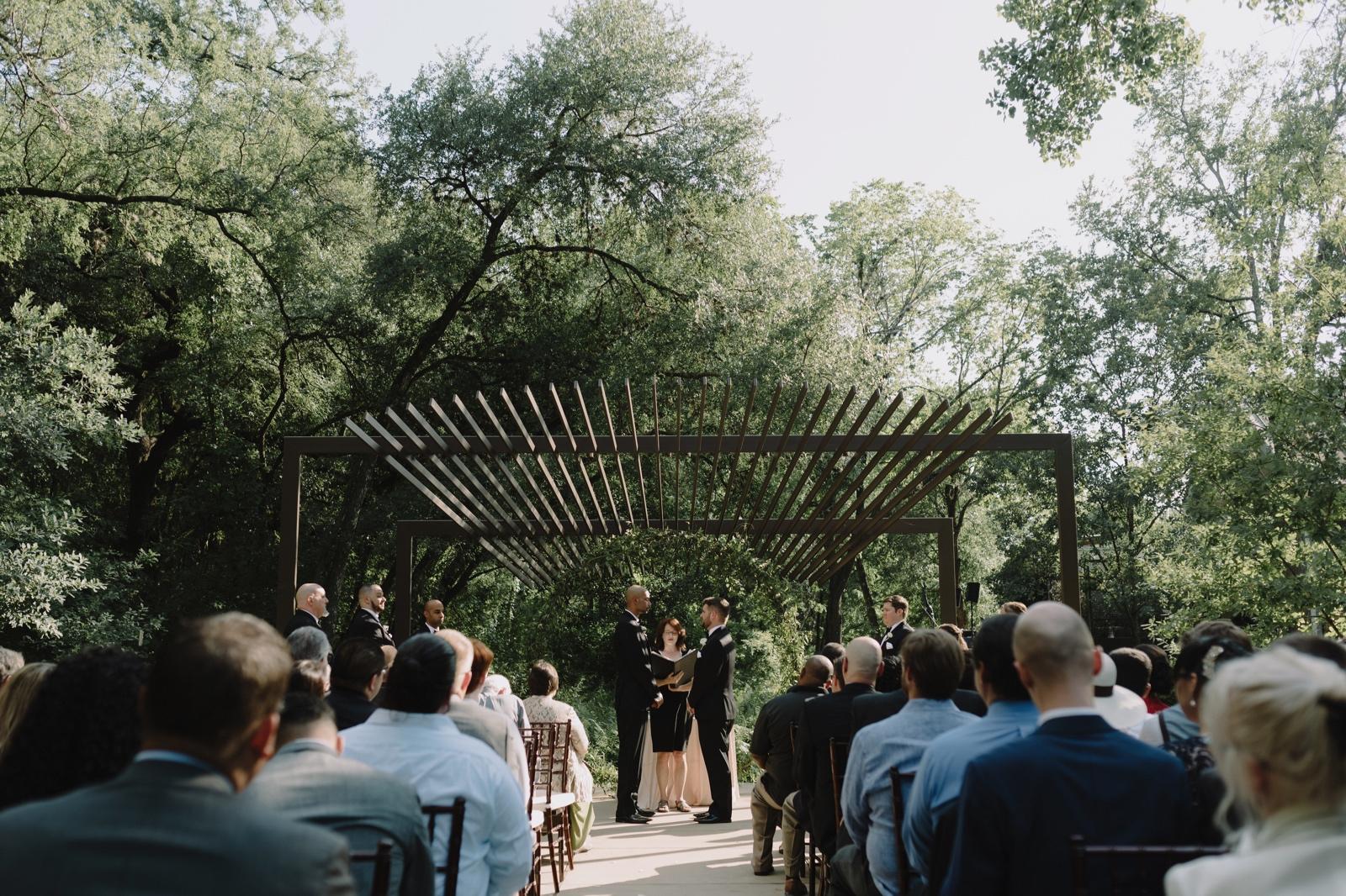 A timeless gay wedding at the Umlauf Sculpture Garden in Austin under the arbor