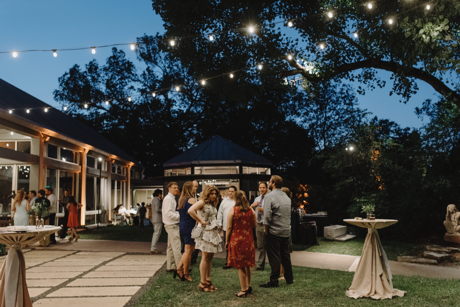 People gathering on the lawn of an outdoor cocktail reception at the Umlauf Sculpture Garden