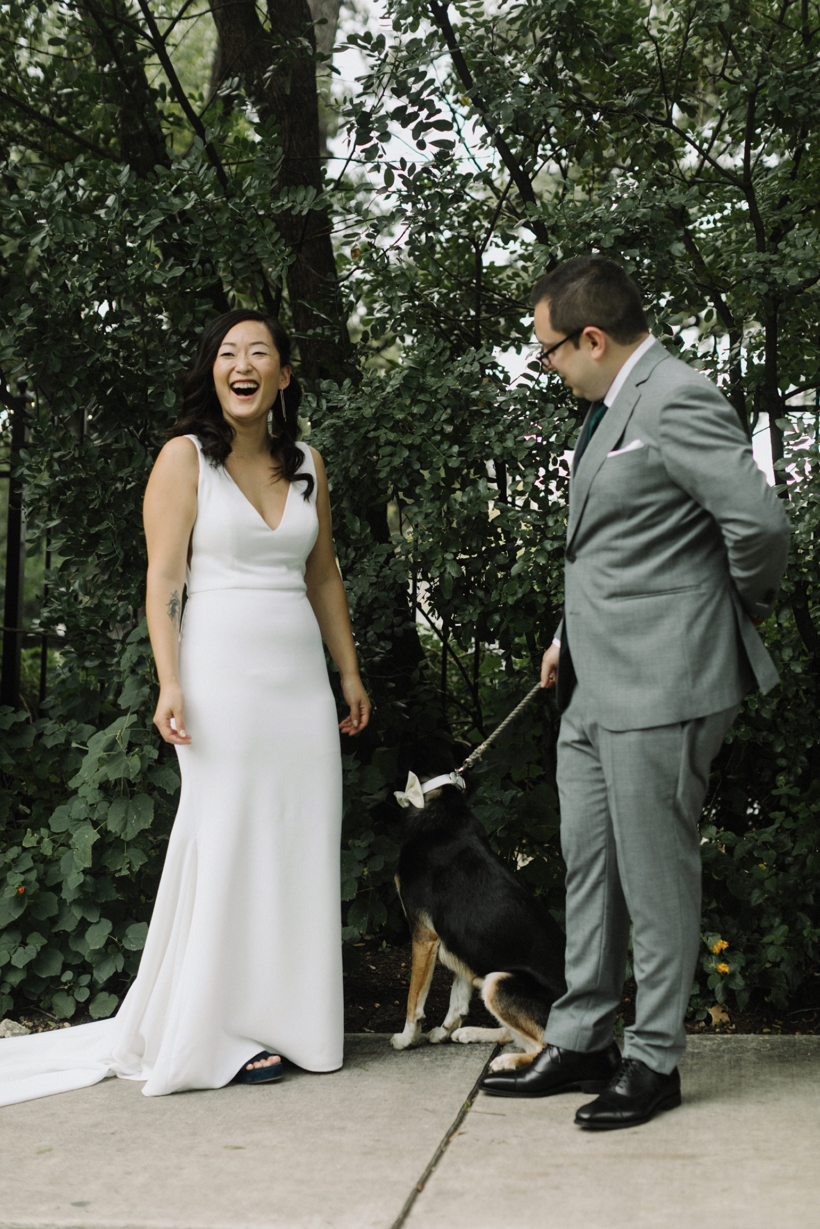 Bride and groom laughign as portraits are taken with their dog