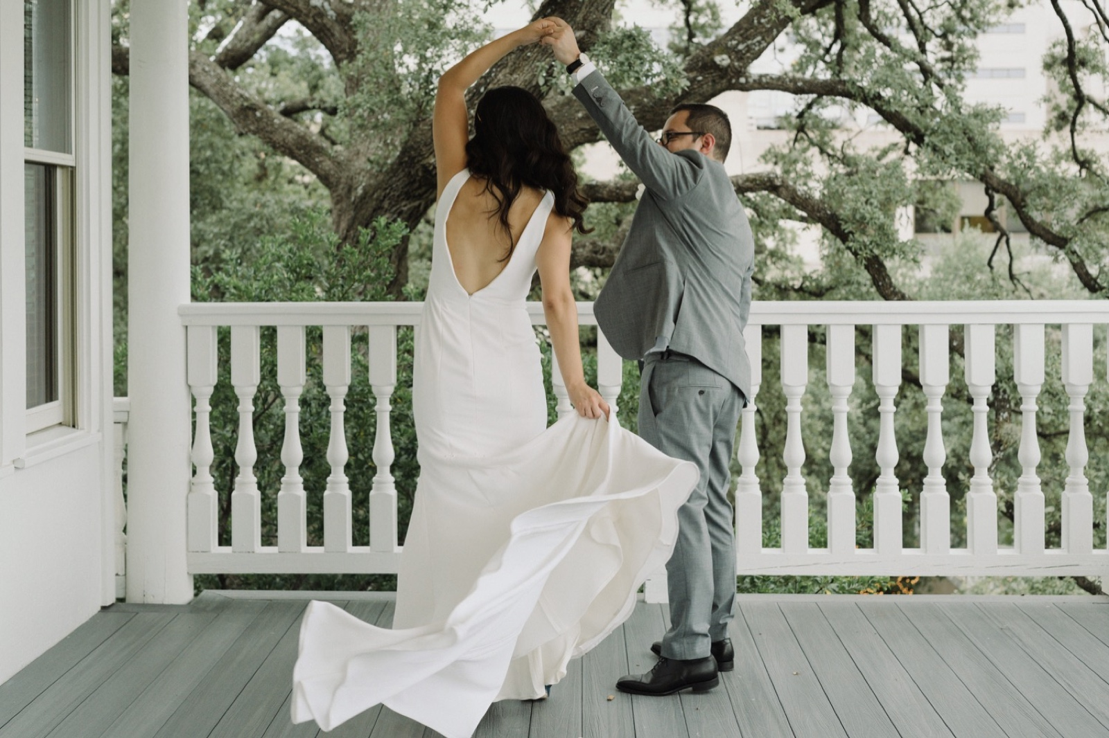 Groom spinning his bride on the patio of the Allen House