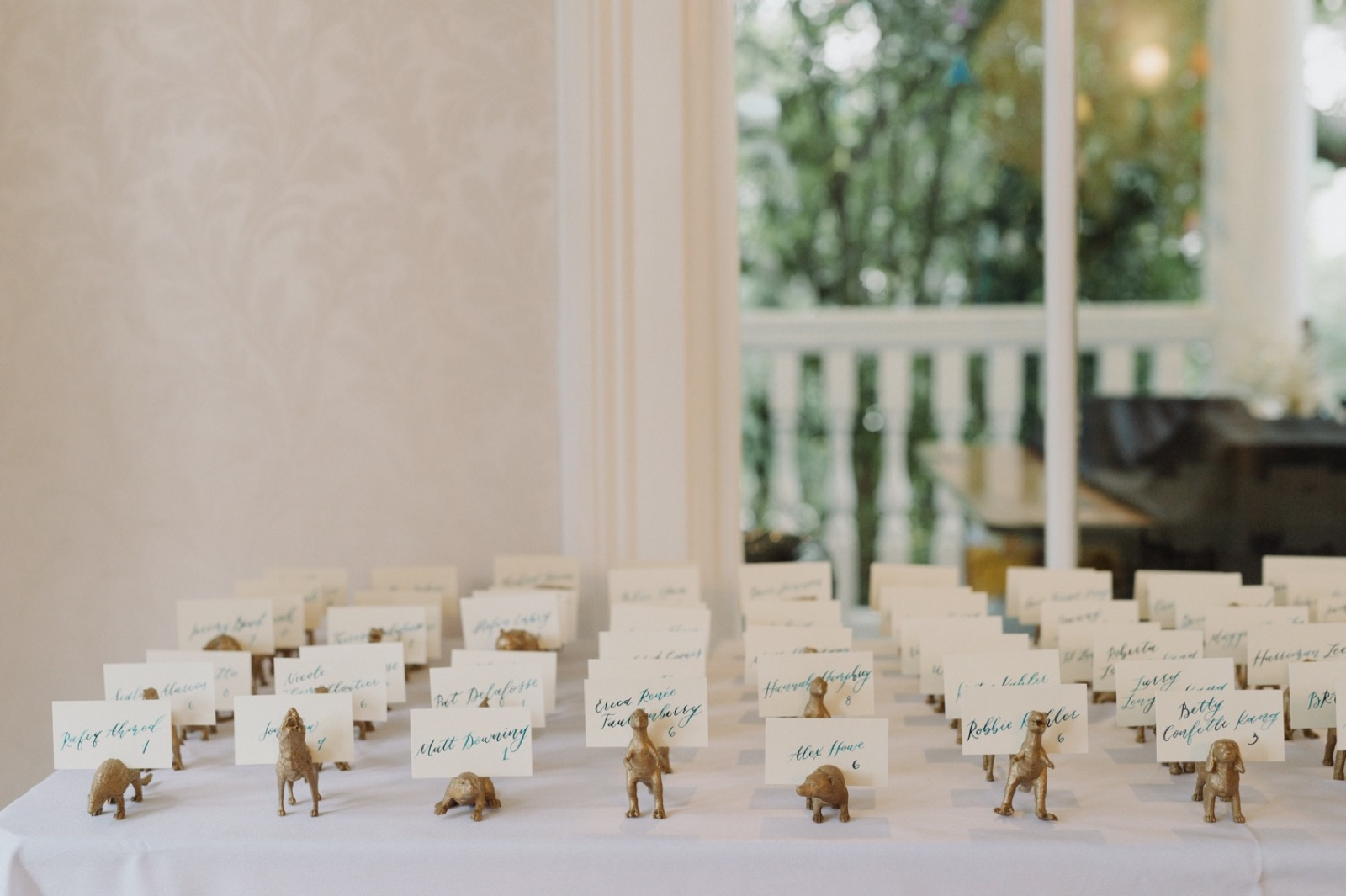 Handmade gold dinosuar name placards for an Allen House wedding