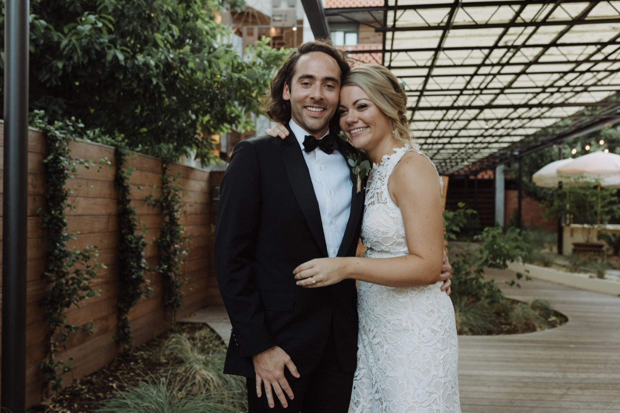 Newly married creative couple embracing in the courtyard after their Carpenter Hotel wedding