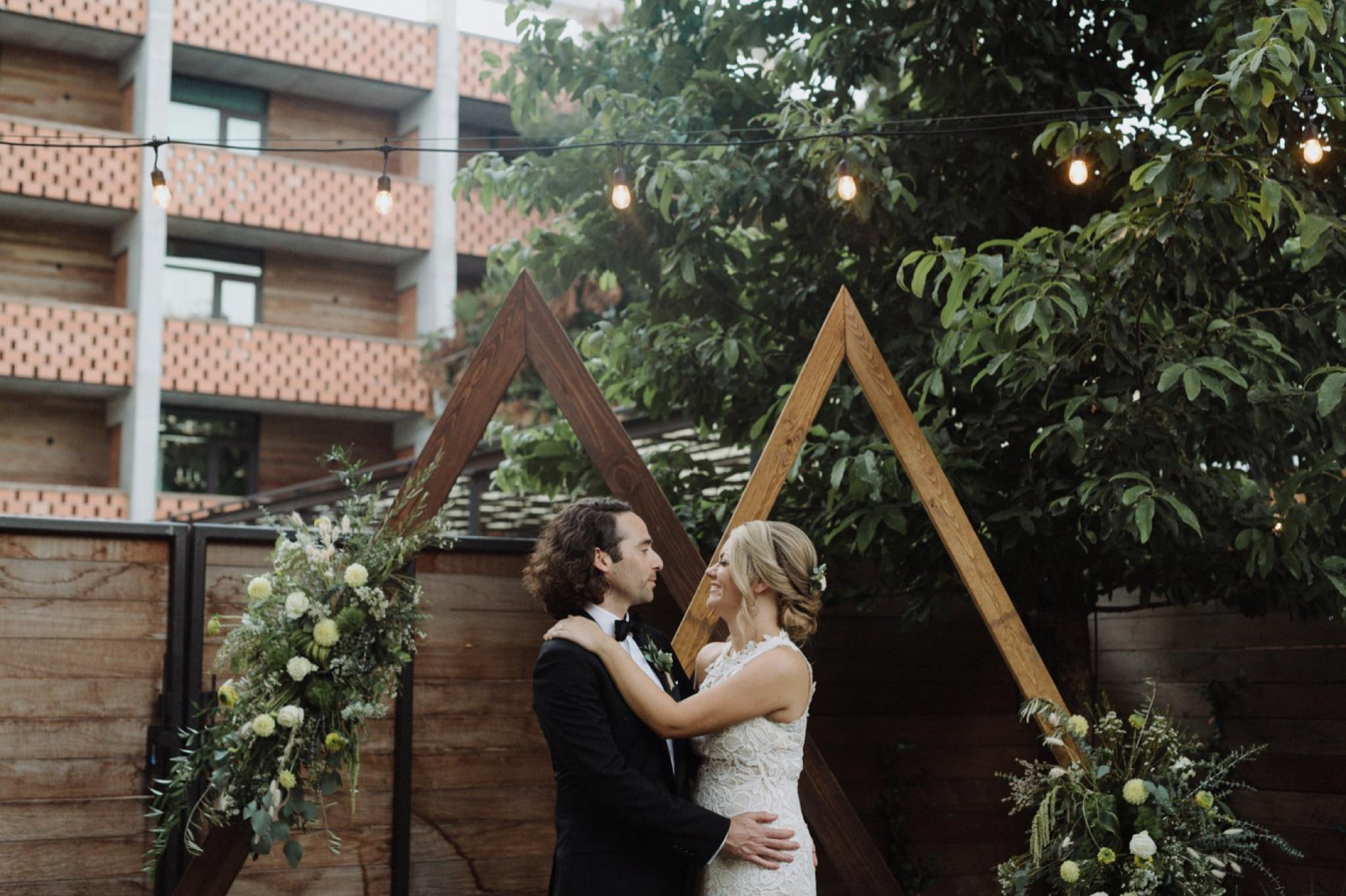 Bride and groom posing with wooden geometric triangle altars with subtle floral details