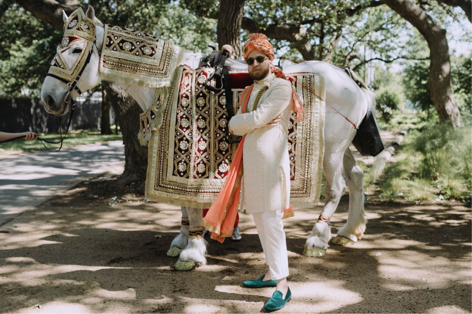 Hindu groom and a decorated white horse from Fantasia Carriage in Austin