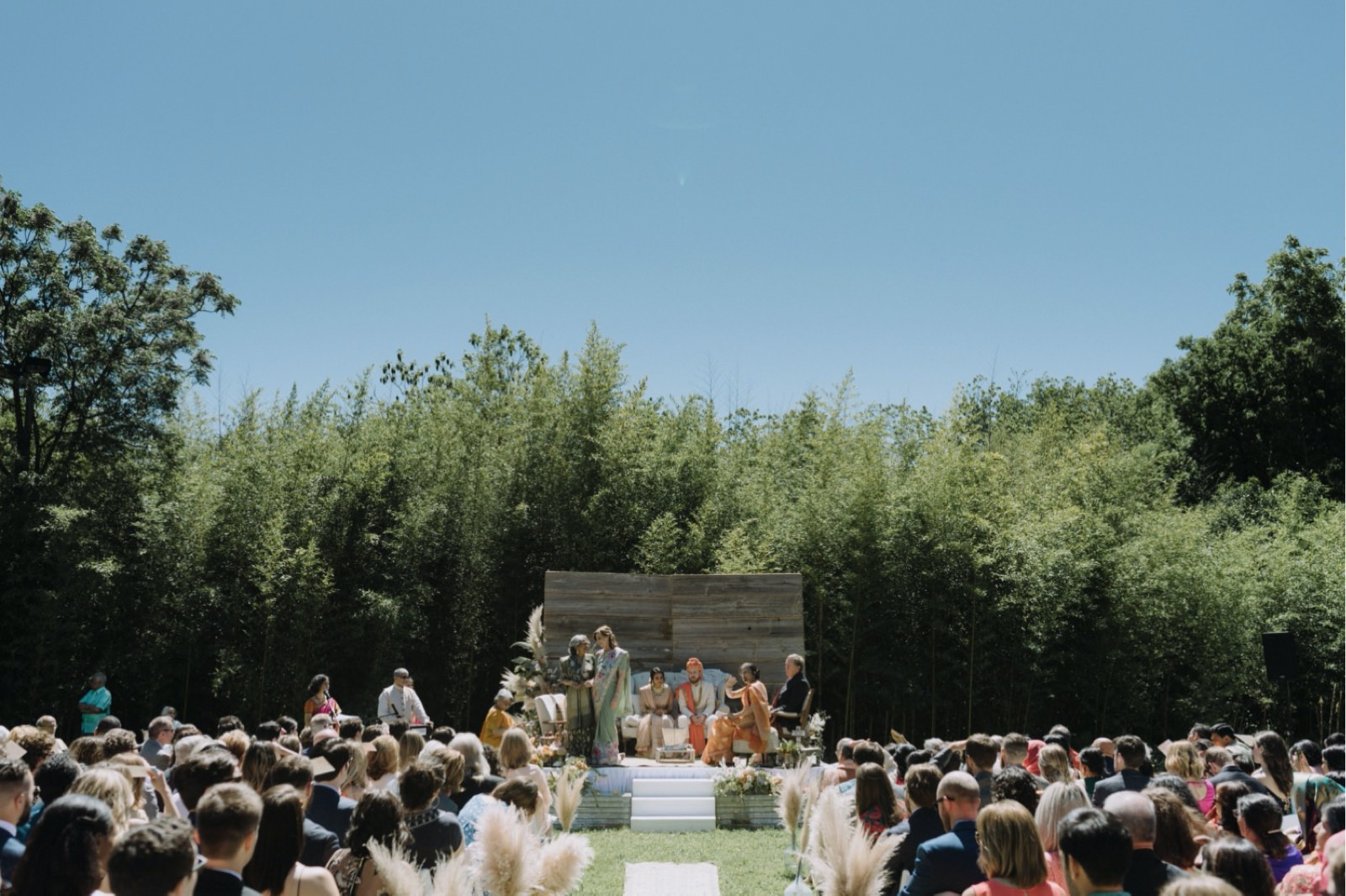Outdoor Hindu ceremony inspiration with bamboo backdrop and wooden wall