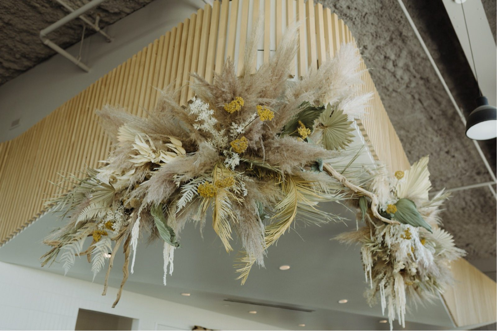 Mounted overhead pampas grass and textured palm floral arch at Austin's favourite coffee shop