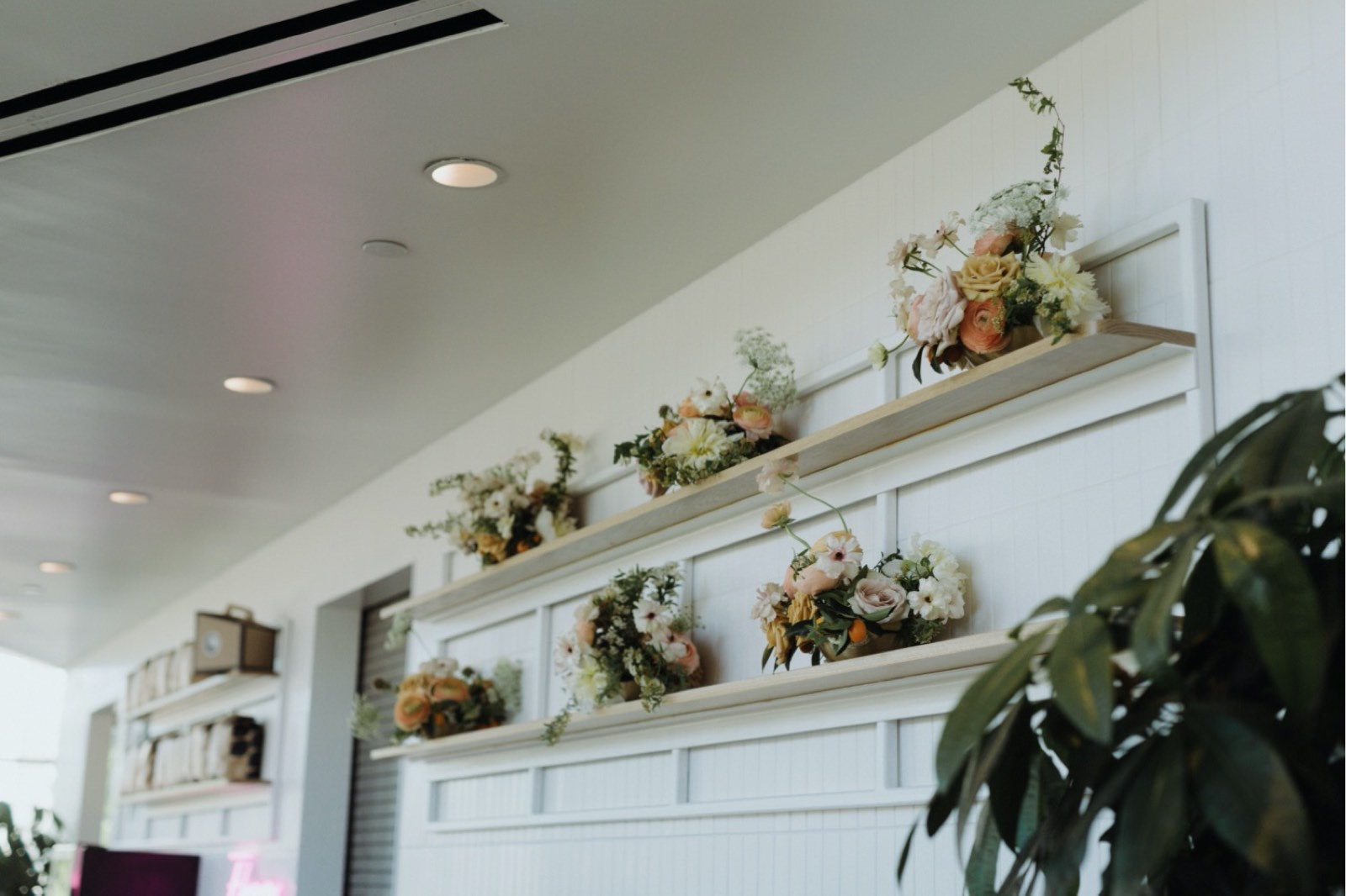 Coral florals lining the wall for a wedding reception at Houndstooth Coffee