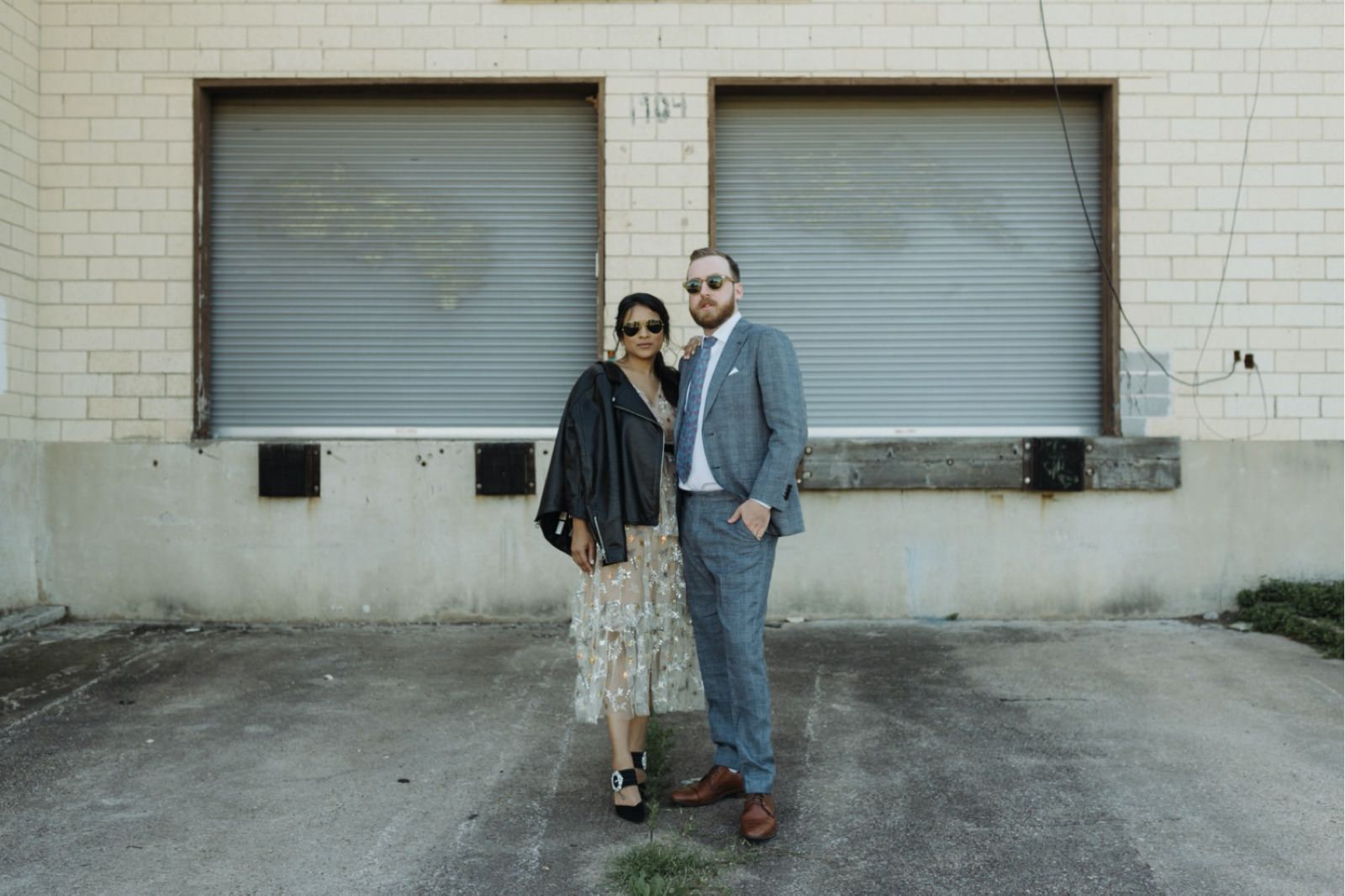 Stylish wedding couple wearing Self-Portrait dress and patterned suit posing in an industrial area of Austin