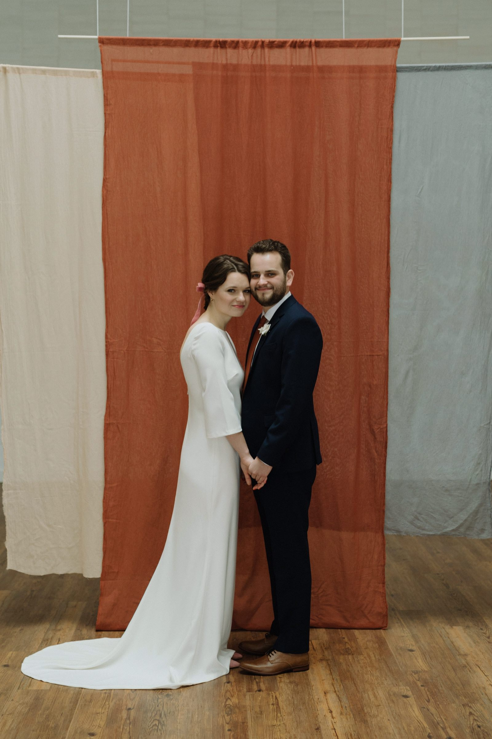 Wedding couple in front of hanging terracotta fabric ceremony installation