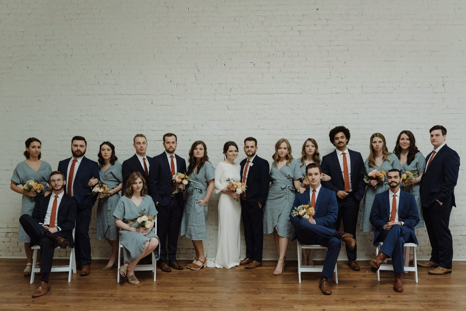 Large wedding party group shot inspiration with blue linen bridesmaid dresses and terracotta ties paired with navy suits