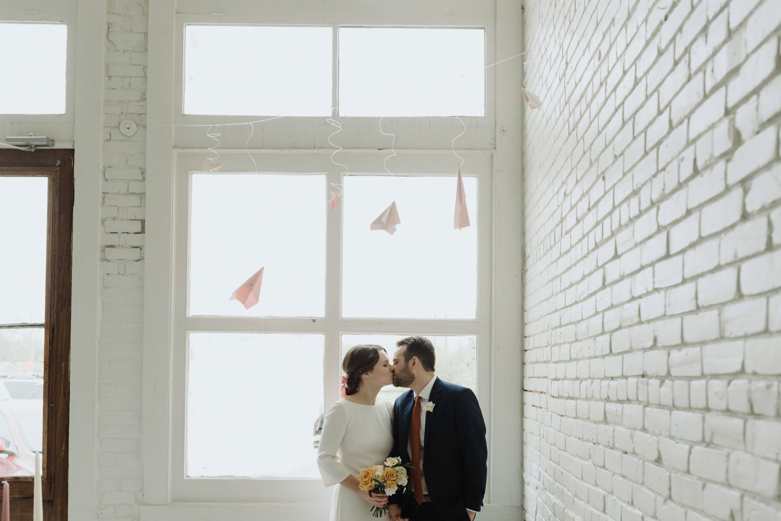 Bride and groom with classic style in front of urban loft window with hanging paper airplanes