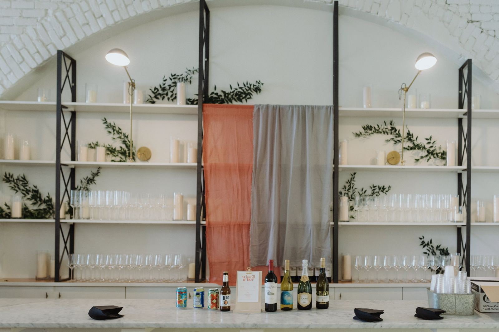 Draped terracotta and blue fabric installation as wedding bar decor