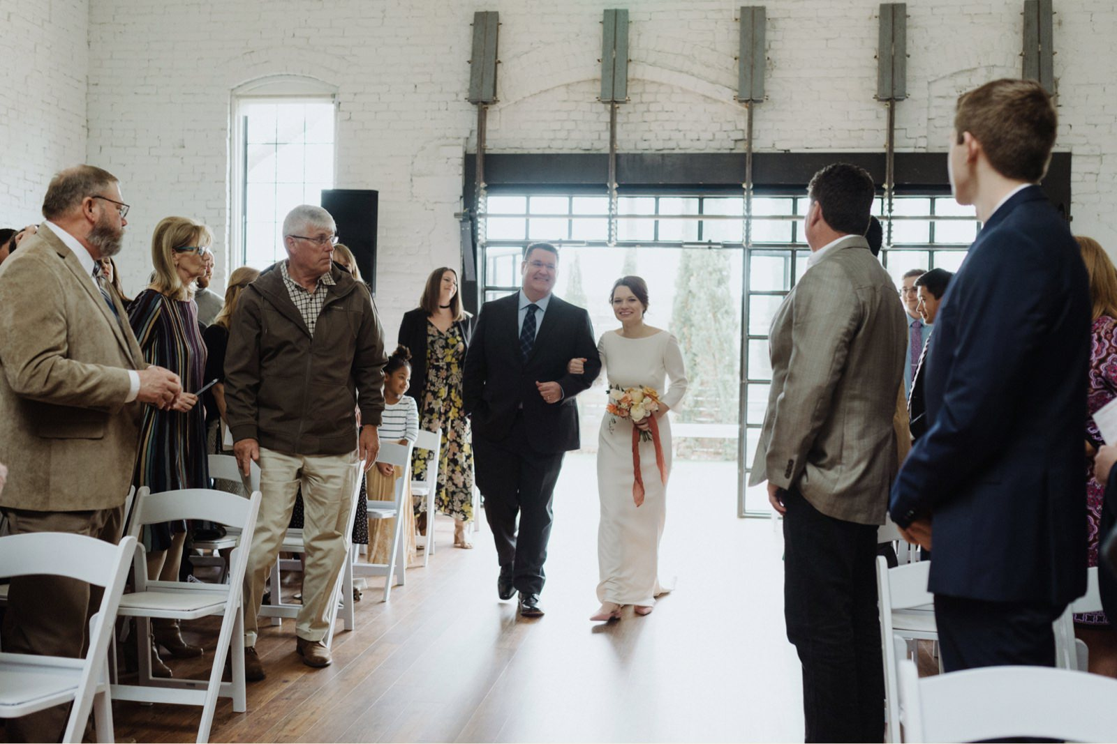 Bride and her fathering entering urban loft ceremony aisle from black industrial doors