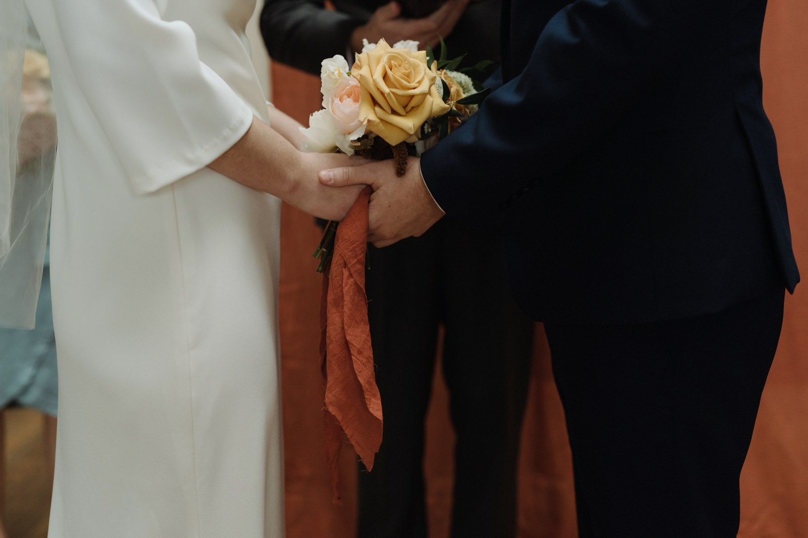 Simple toffee and coral bridal bouquet with terracotta fabric ribbon
