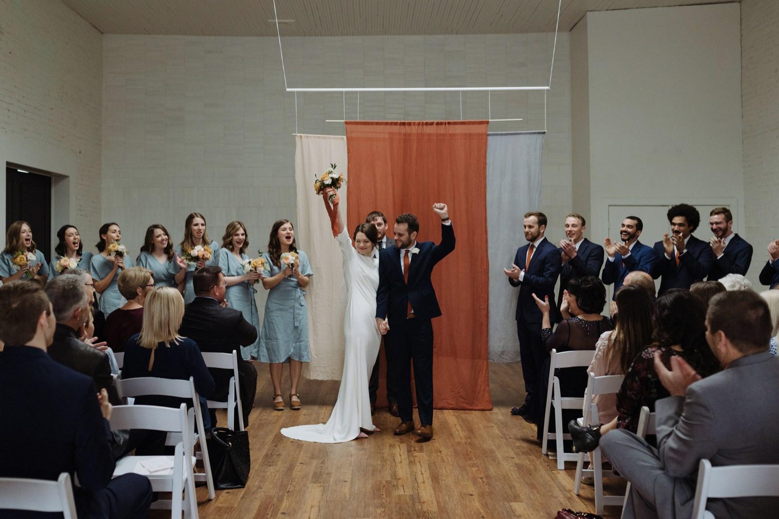 Draped earthy-toned fabric ceremony backdrop for an urban loft wedding near Austin