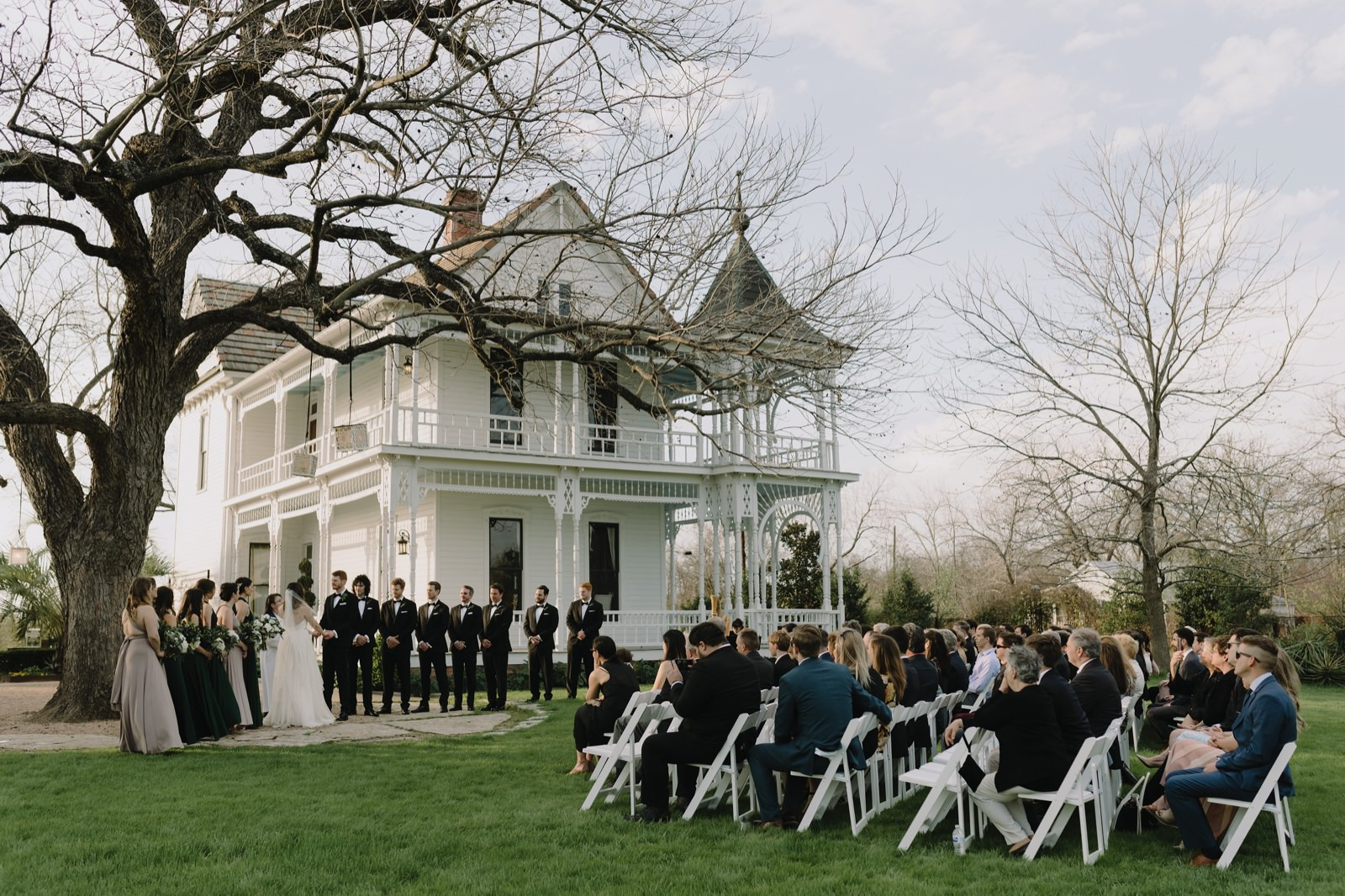 Barr Mansion's ceremony under the pecan tree with a white mansion backdrop