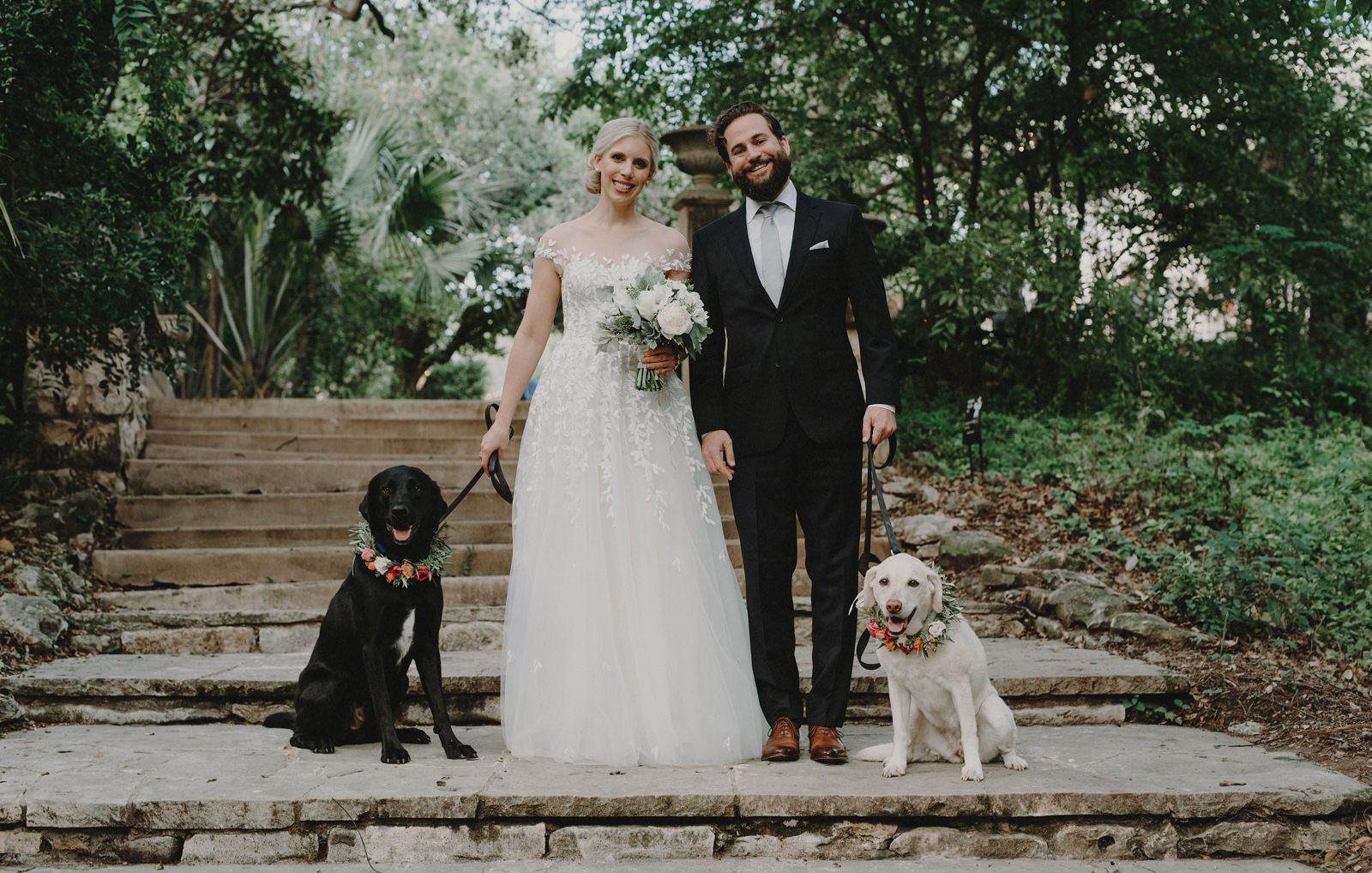 Wedding couple with their dogs wearing rose floral collars in the gardens of Laguna Gloria