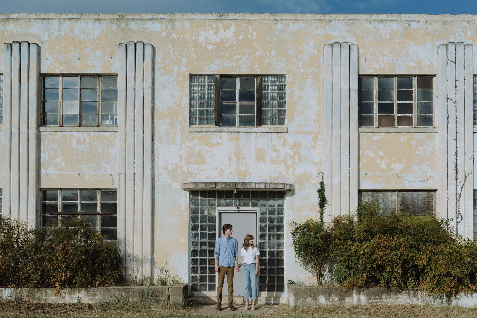 Art deco revivalist building backdrop for an industrial interior Austin engagement session with a stylish couple