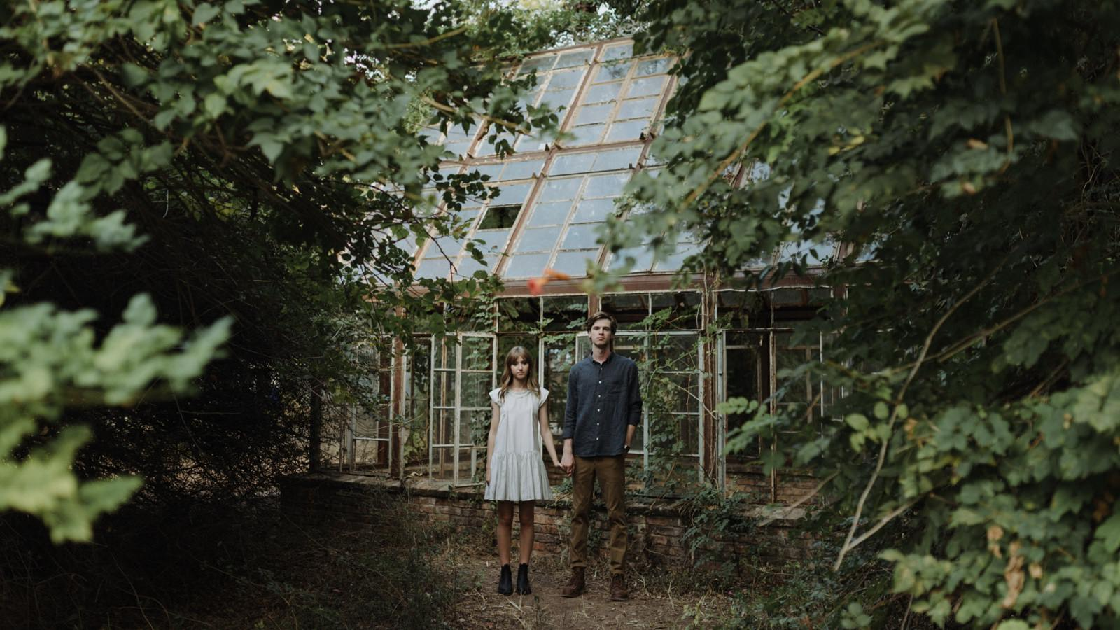 Engagement session couple framed by foliage in front of the greenhouse at Sekrit Theater