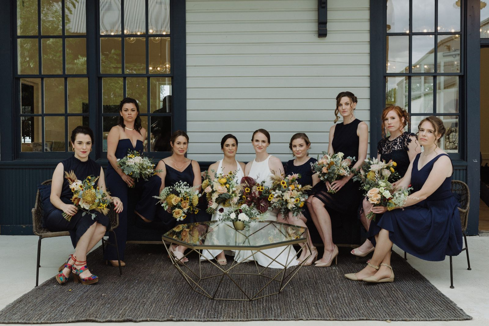 All women wedding party for an LGBTQ wedding in Austin with unique navy dresses and pantsuits and toffee and soft pink bouquets