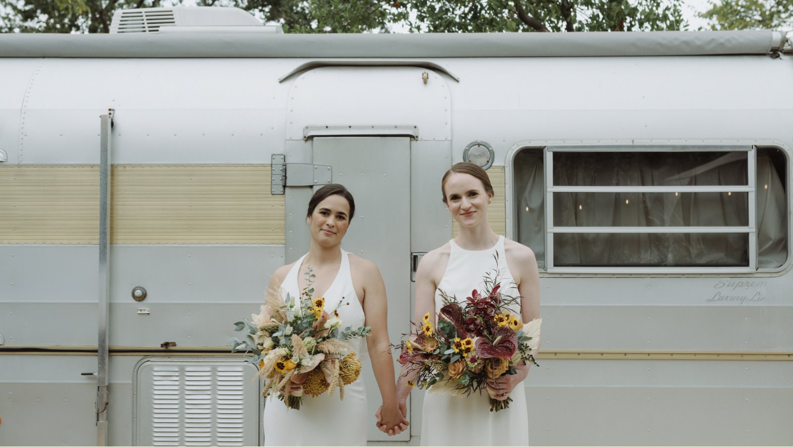 Brides holding hands in front of the trailer at Springdale Station