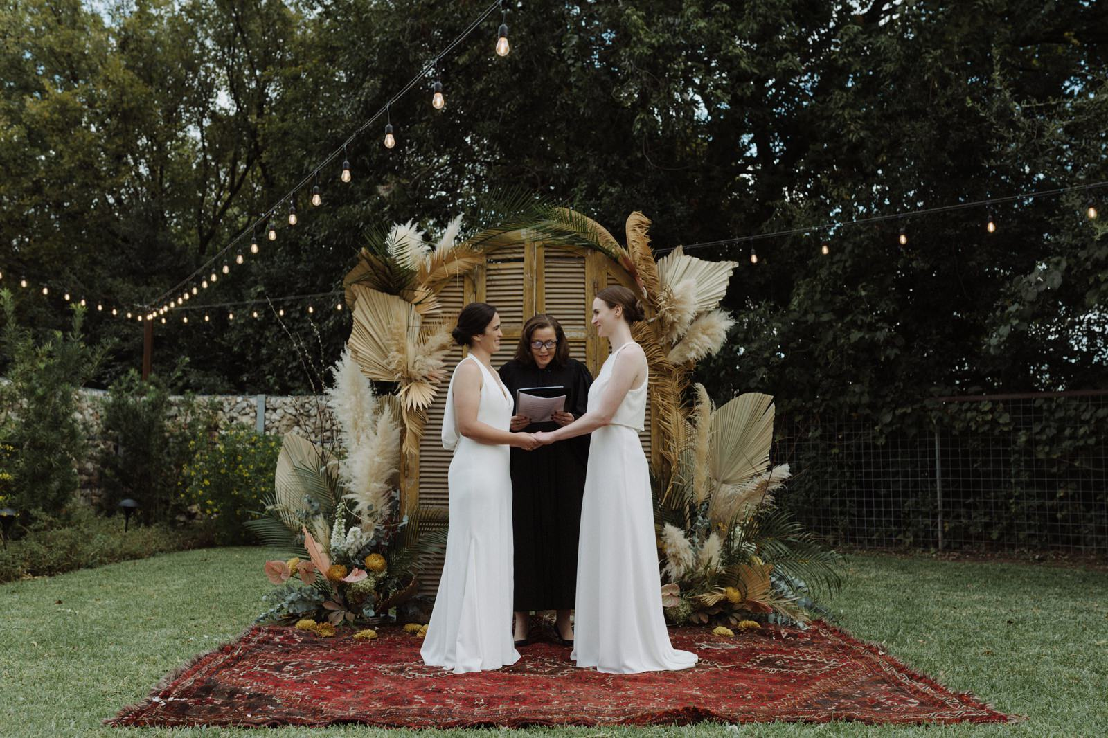 Outdoor courtyard ceremony with boho inspired decor by Rosehip Flora in Austin