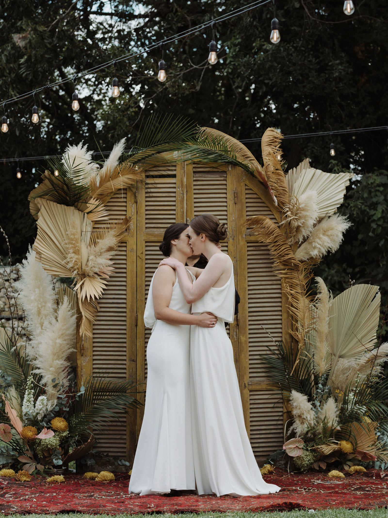 Two brides first kiss at an altar decorated with dried palm fronds, pampas grass, and subtle mustard and pink florals on a red rug