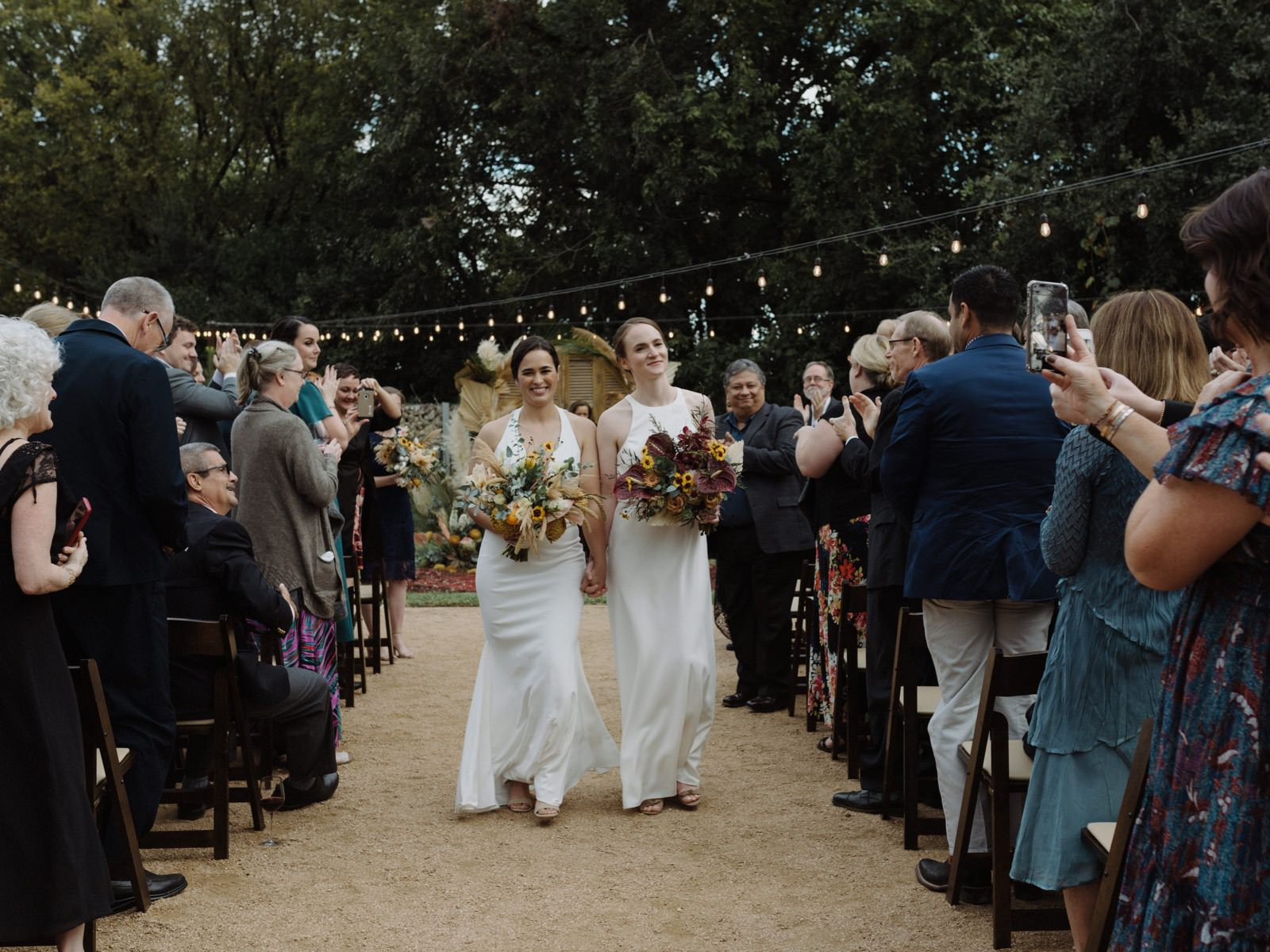 Wedding recessional in Springdale Station's outdoor courtyard with two brides holding complimentary yet unique textured bouquets