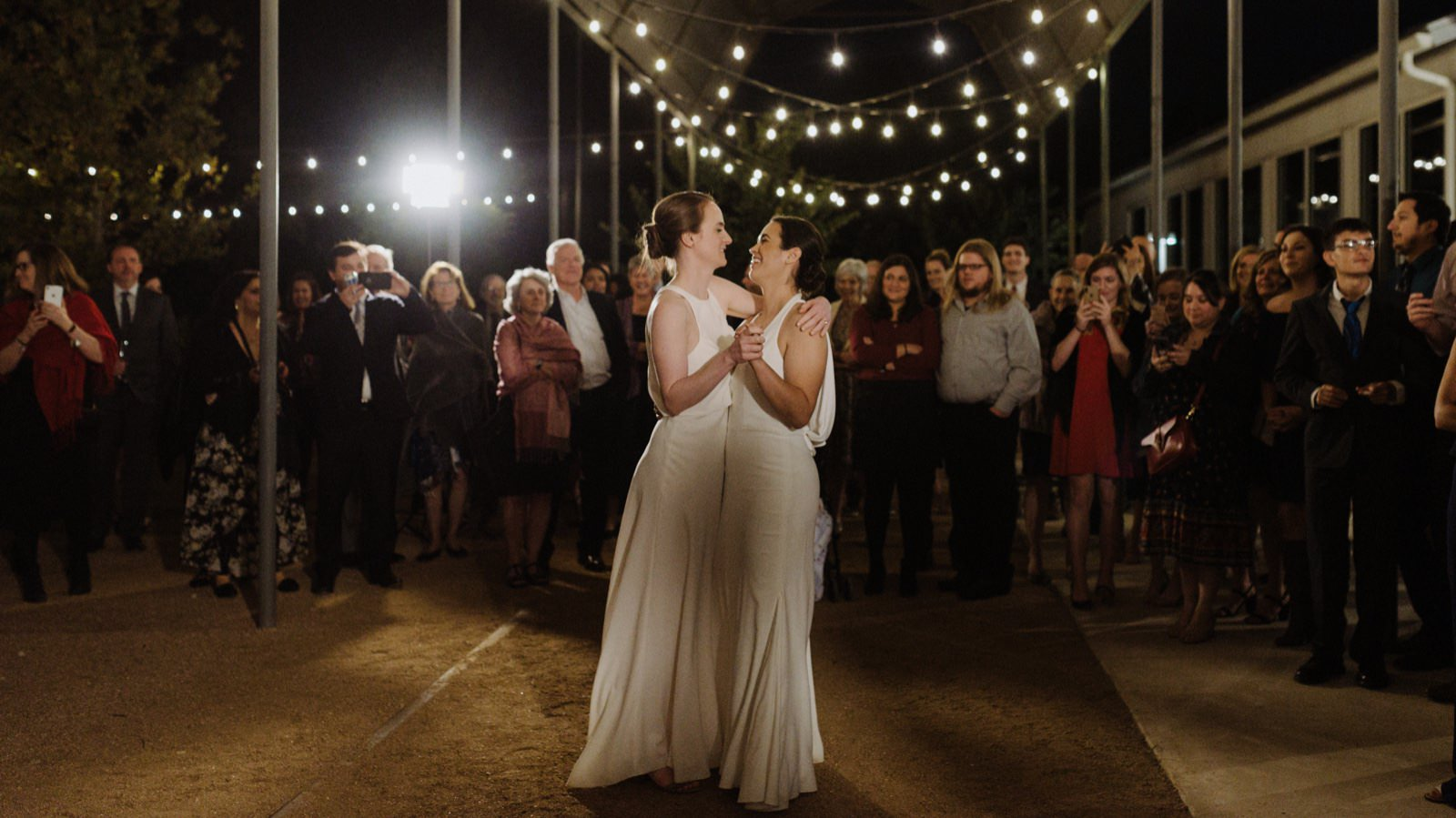 Two brides dancing under fairy lights at their Springdale Station wedding as their family and friends look on