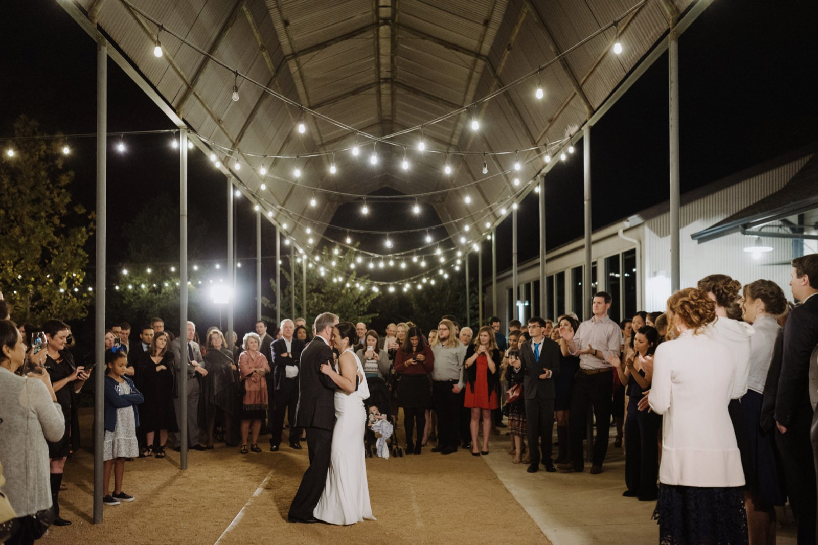 Father daughter dance under string lights on the tracks at Springdale Station