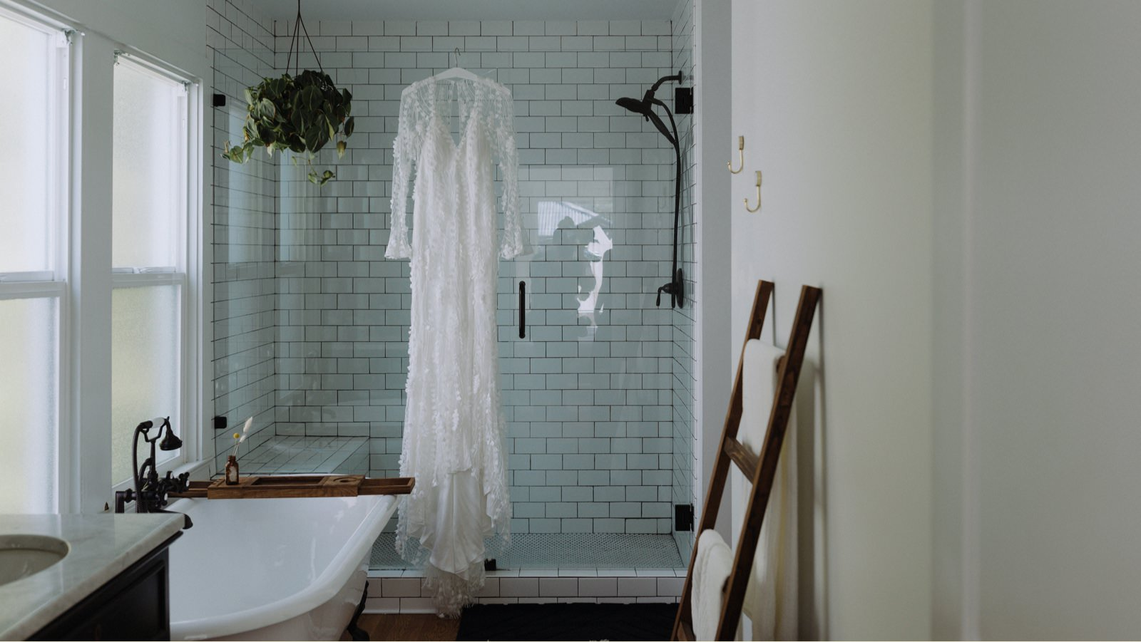 Alexandra Grecco's off-white Dylan wedding gown hanging on the glass shower in a titled bathroom, with subtle bell sleeves