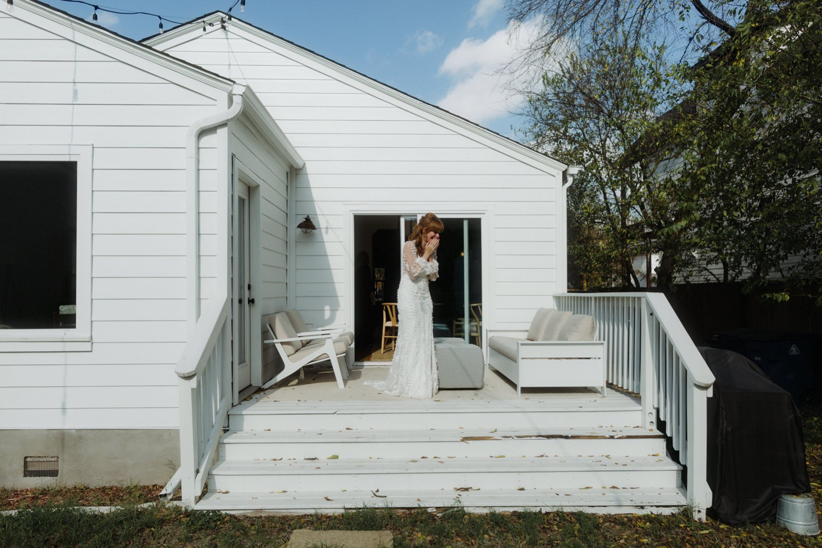 Bride on the back porch of the Monroe Bungalow in Austin holding her face in excitement as she sees her groom at the first look