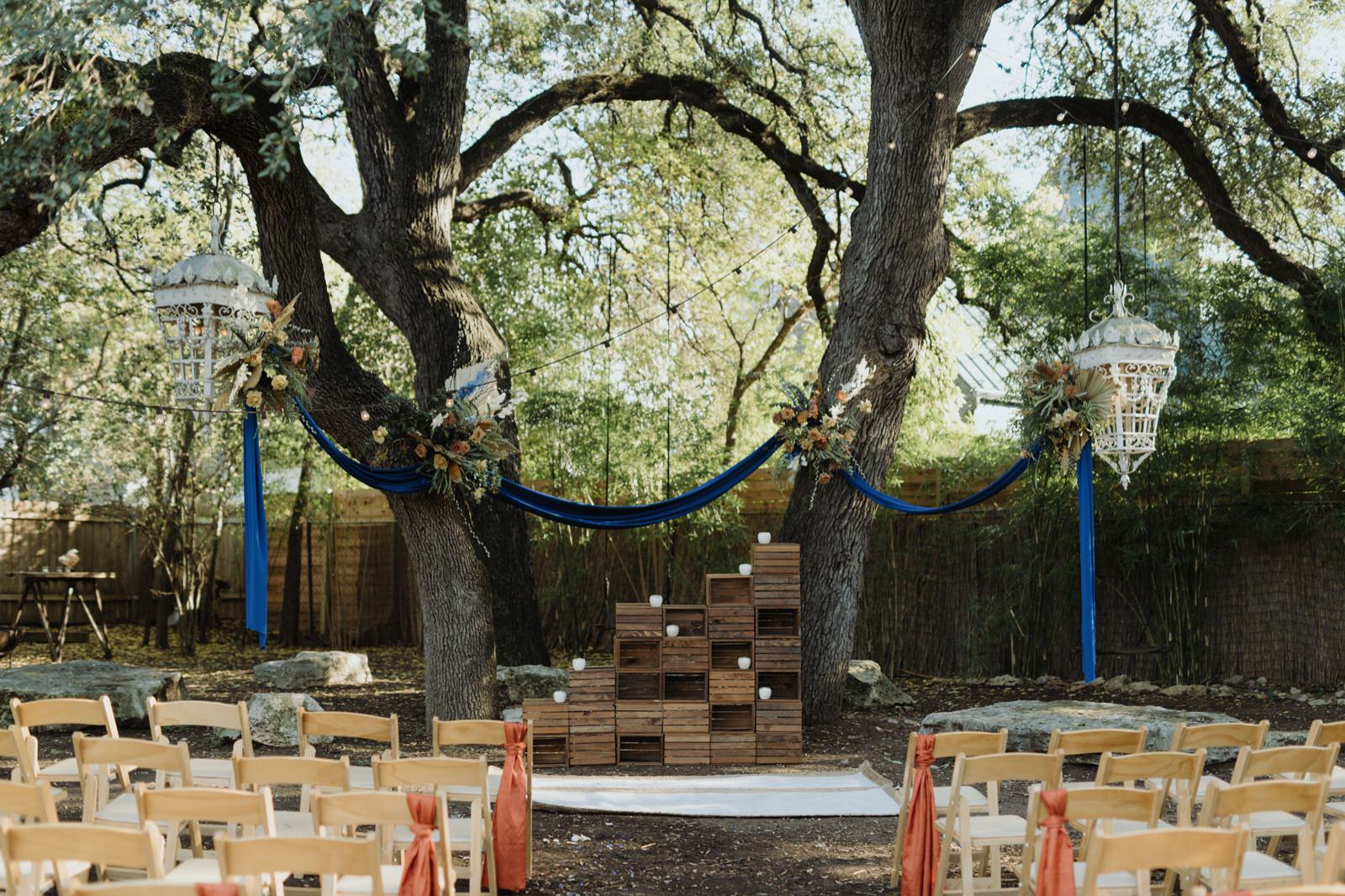 Royal blue draping and florals by Rosehip Florals in the trees at Vuka at Bouldin Creek's wedding ceremony location