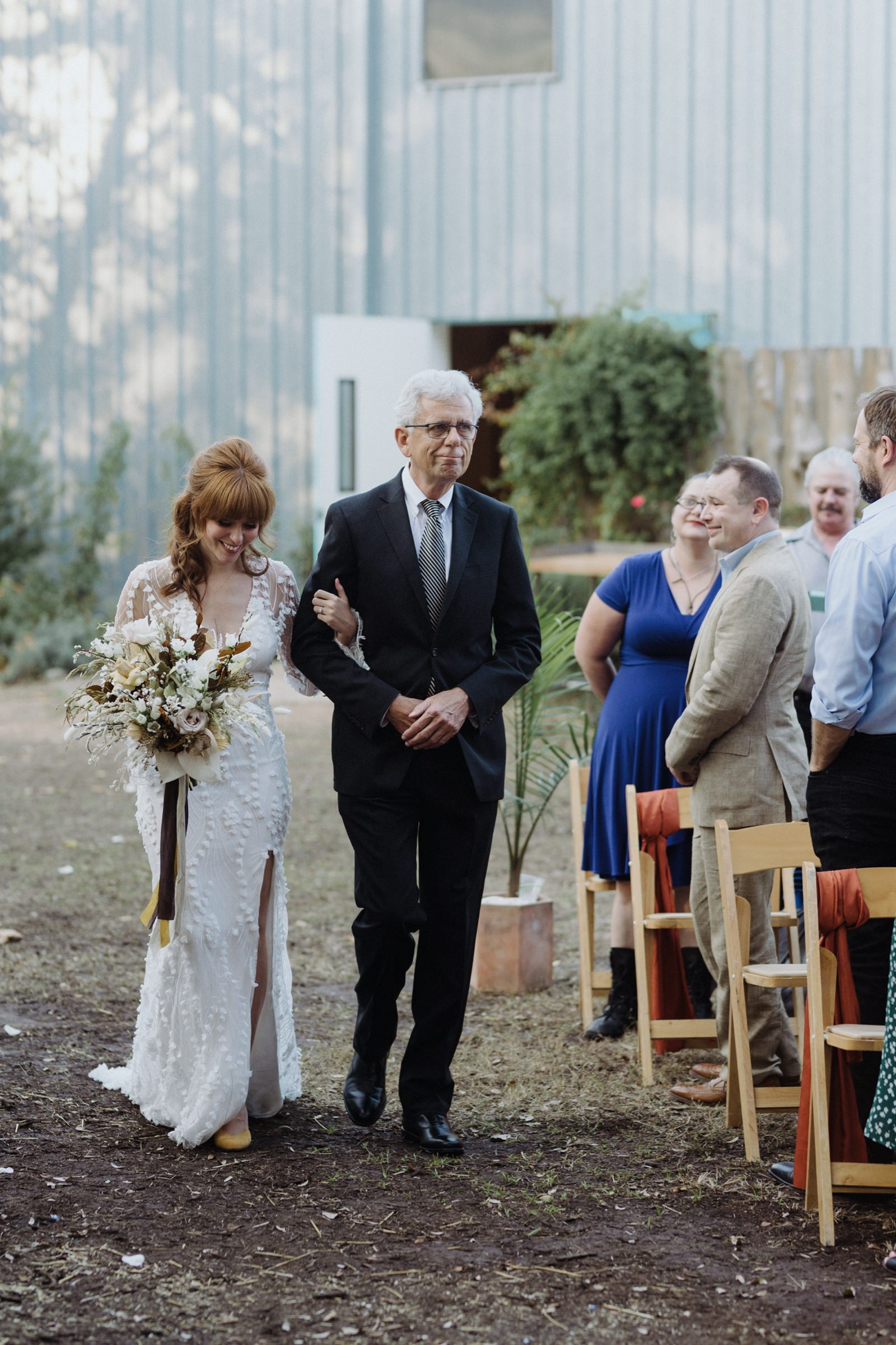 Father of the bride tearing up as he walks his daughter wearing Alexandra Grecca's Dylan gown down the outdoor aisle at Vuka Bouldin Creek
