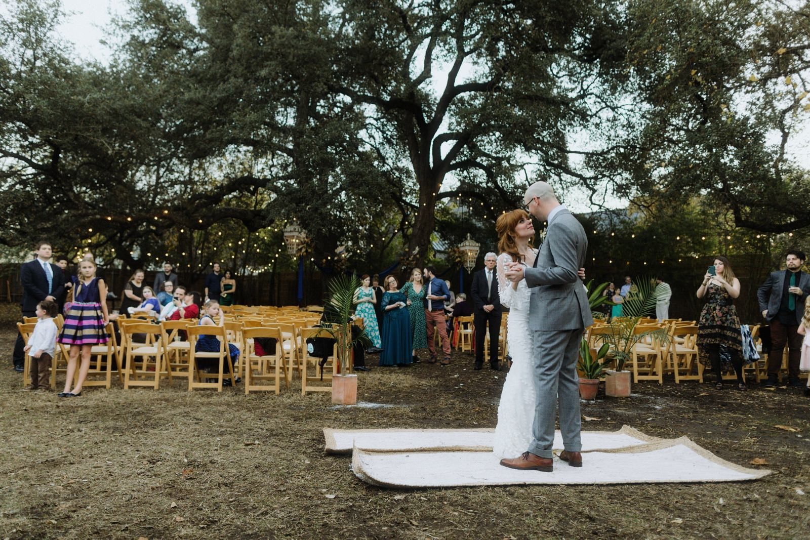 Outdoor first wedding dance at Vuka at Bouldin creek with couple holding hands dancing on a rug