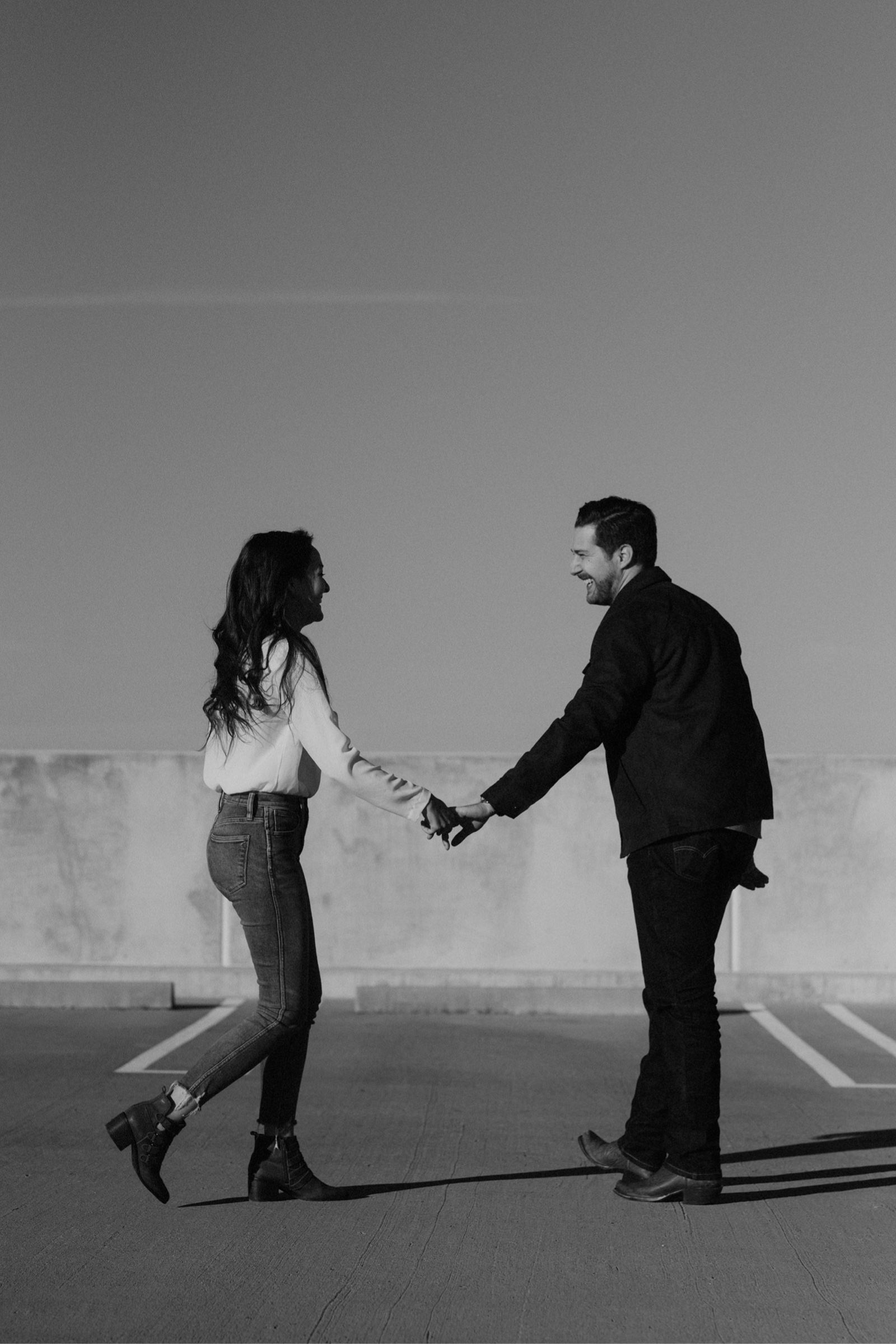 Couple holding hands as they walk side by side on a parking structure in Austin