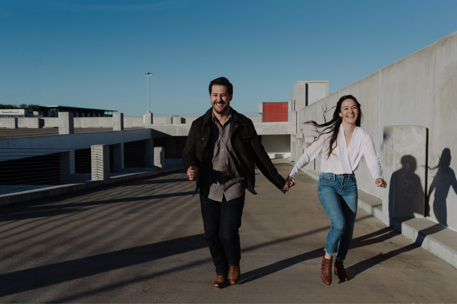 Engaged couple joyfully running hand in hand up an empty parking lot structure